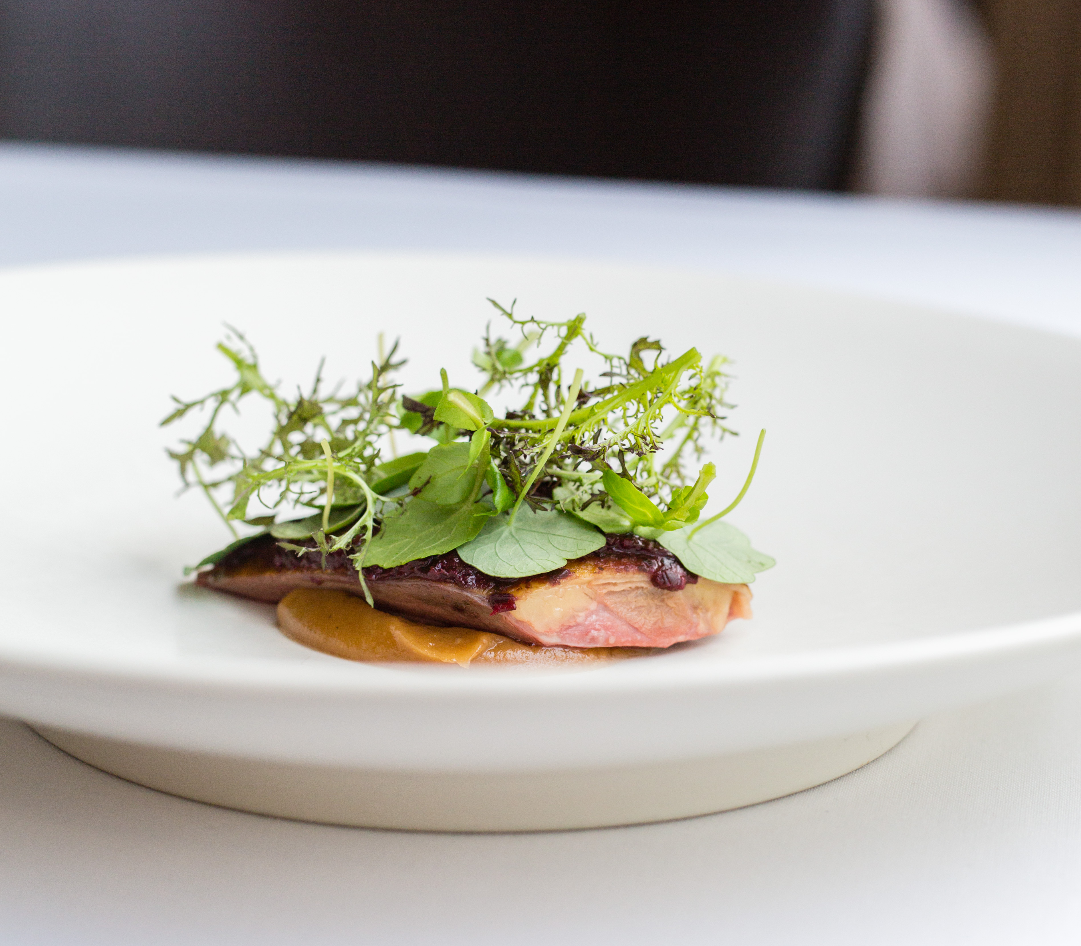A piece of duck topped with greens at Castagna