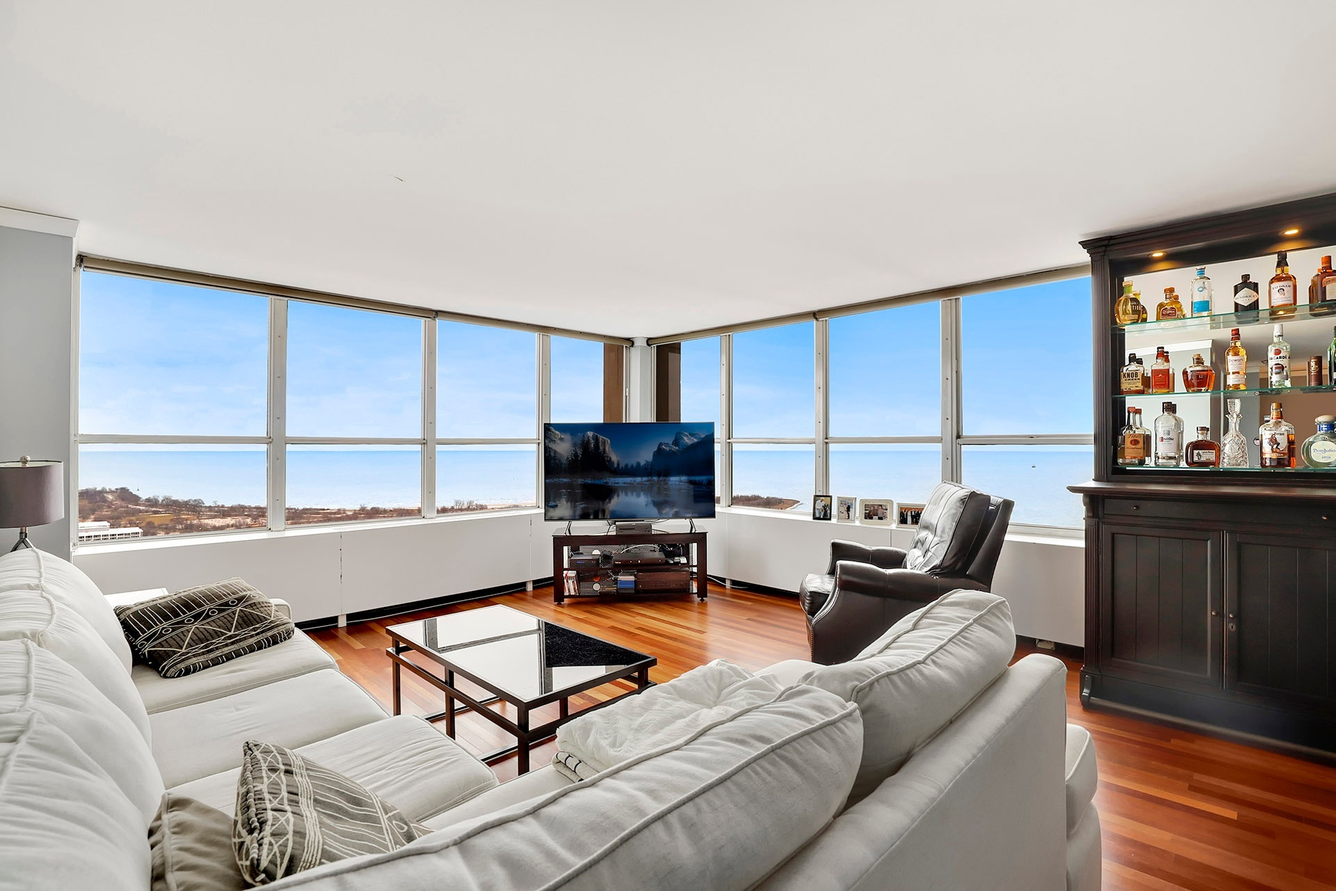 A living room with hardwood floors, a gray sectional couch, and two walls of windows with views of Lake Michigan.