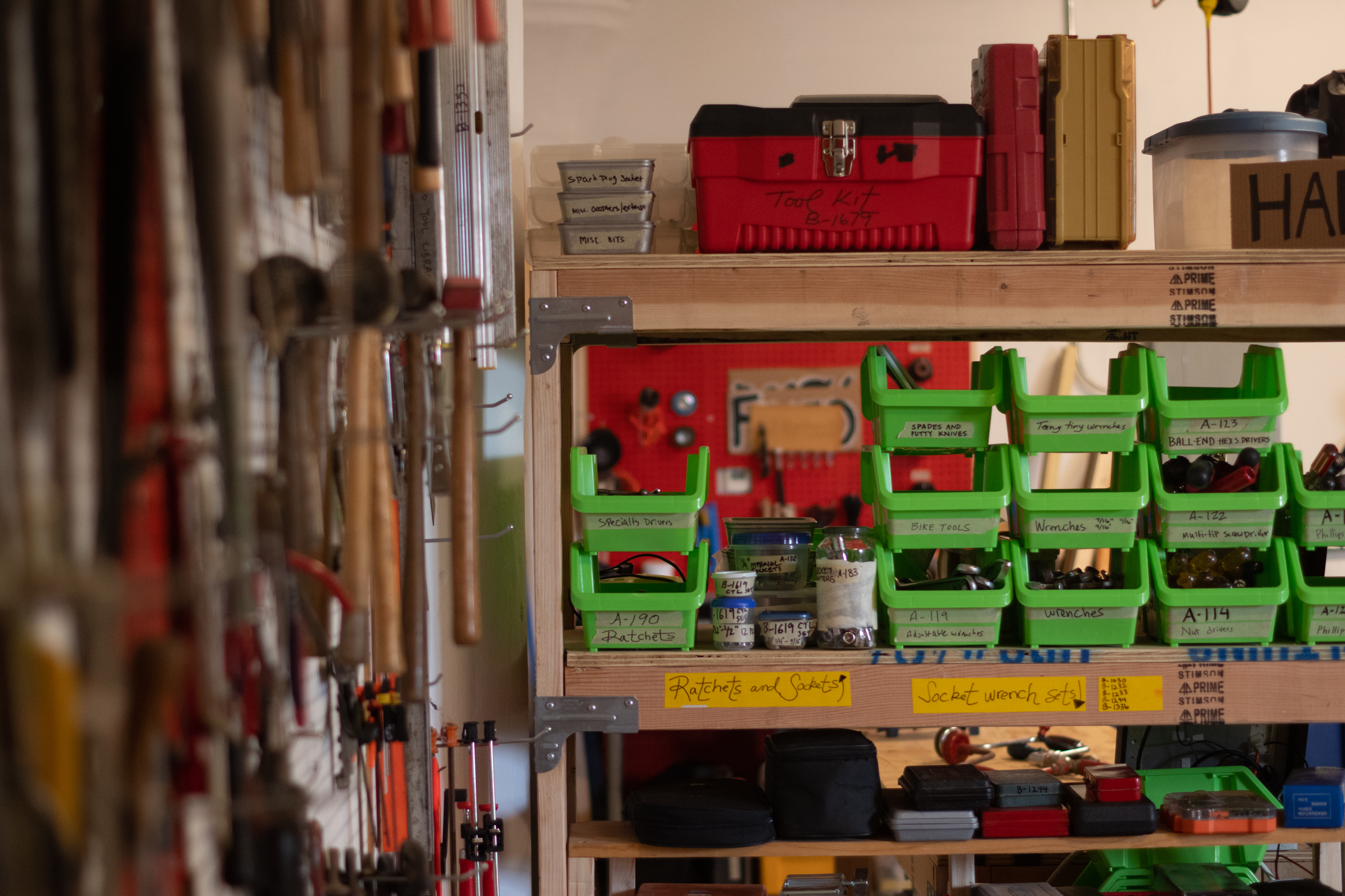 A photo of green bins with tools, wooden shelves, and red tool boxes.