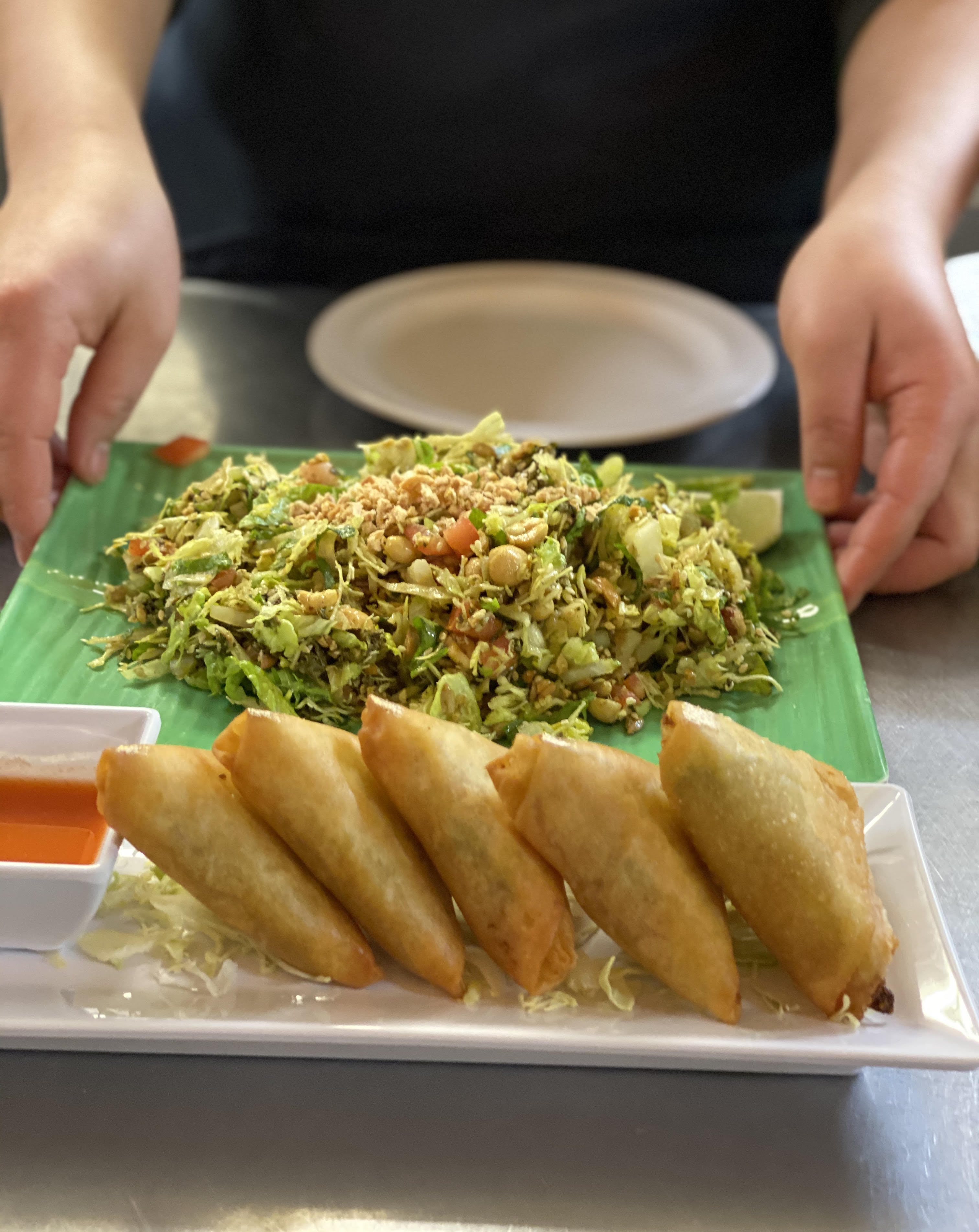 A white plate with five samosas sits next to a white  container of dipping sauce. A green plate of a chopped, slaw-like salad sits behind it, being placed by two hands