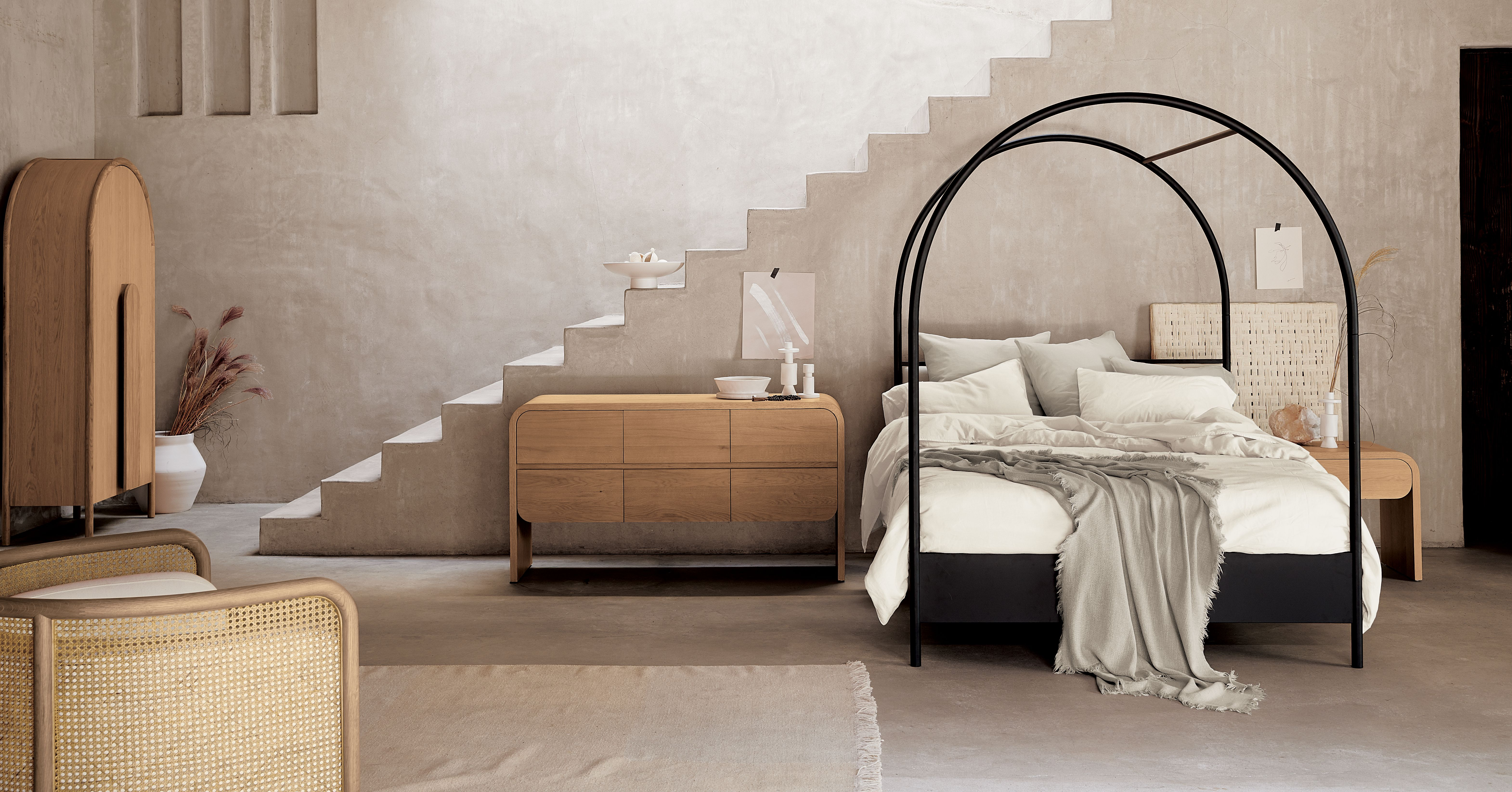 Canopy bed in bedroom with round arches.