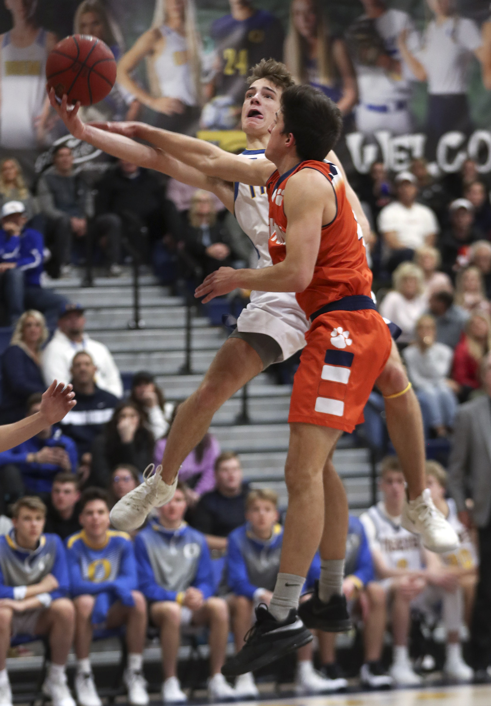 Orem's Taft Mitchell scoops up a shot for a basket and is fouled by Brighton's Justin Devashrayee during a 5A playoff basketball game in Orem on Friday, Feb. 21, 2020.