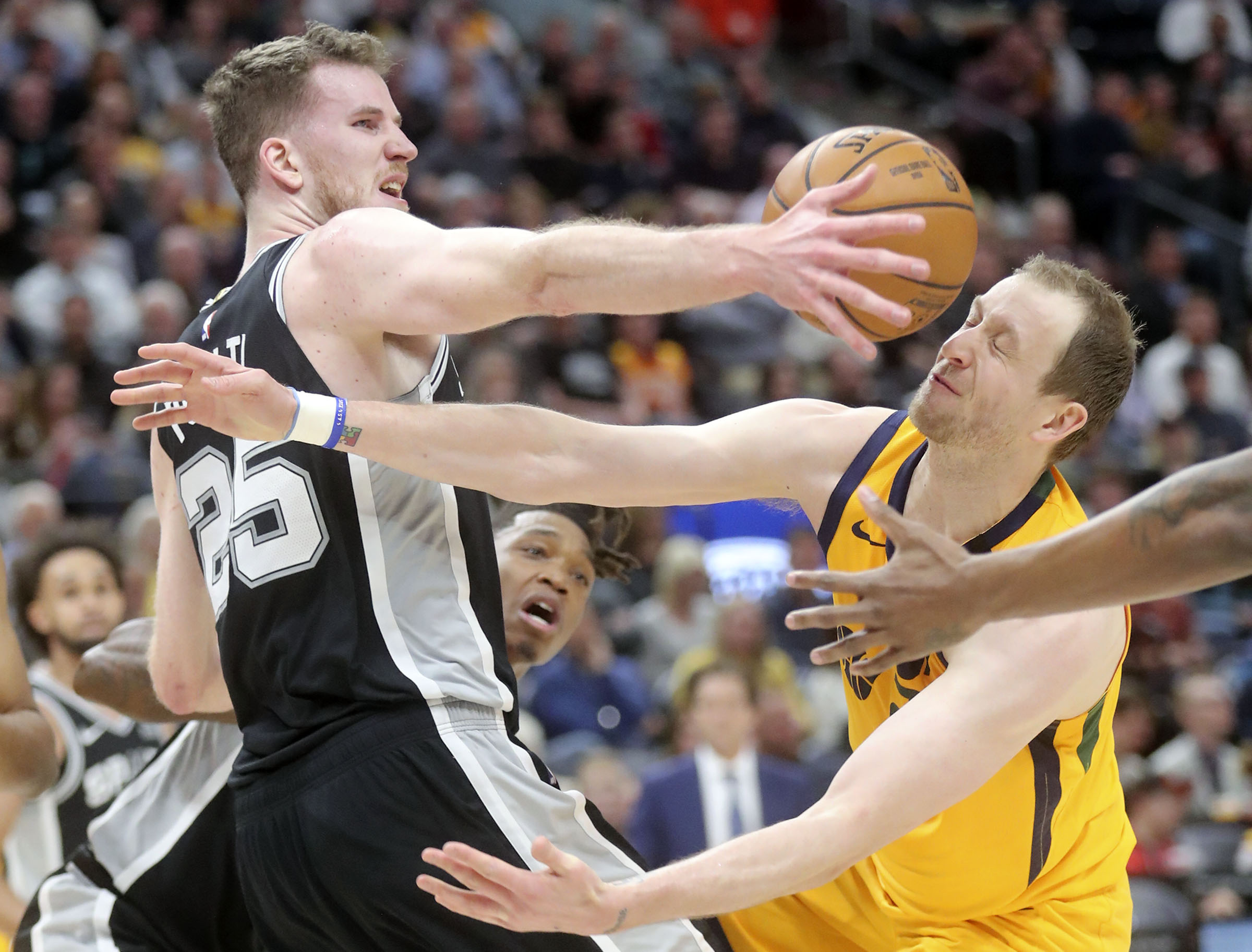 Utah Jazz guard Joe Ingles (2) loses the ball as San Antonio Spurs center Jakob Poeltl (25) reaches for it during an NBA game at Vivint Arena in Salt Lake City on Friday, Feb. 21, 2020.The Jazz lost 104-113.