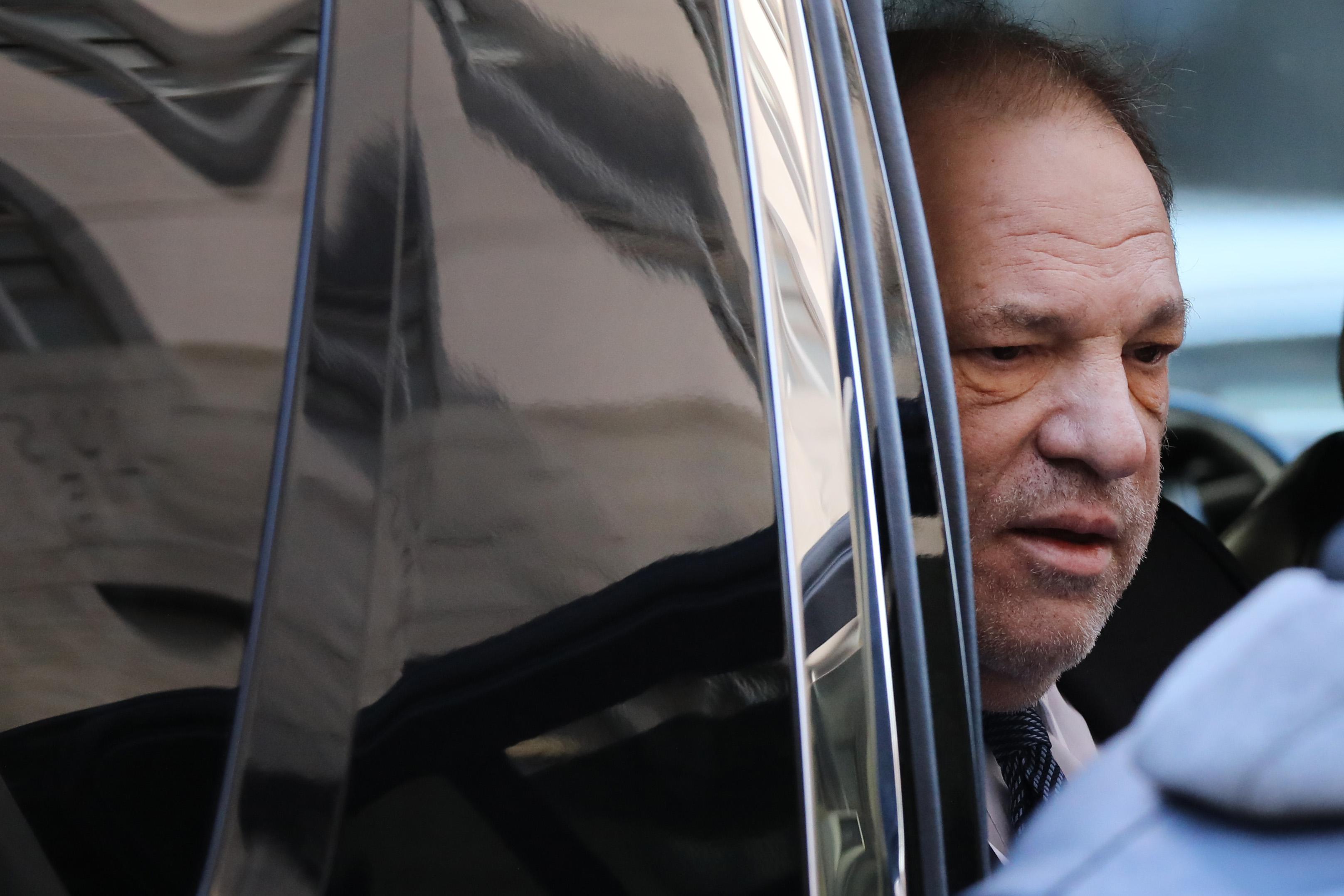 Harvey Weinstein's face seen through the open window of a car.