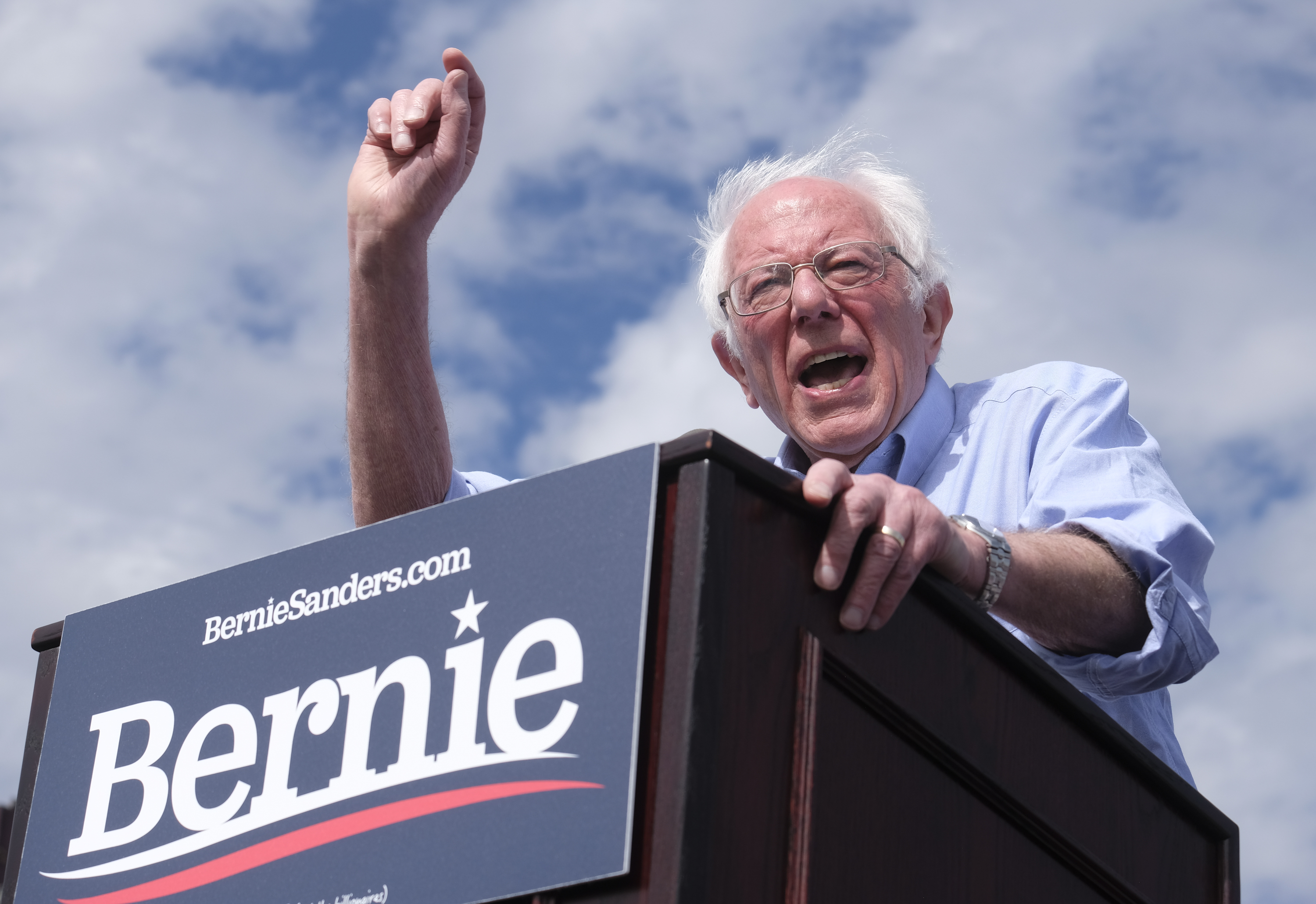 Sanders gestures, shouting, at a podium bearing his name under a blue sky dotted with white clouds.