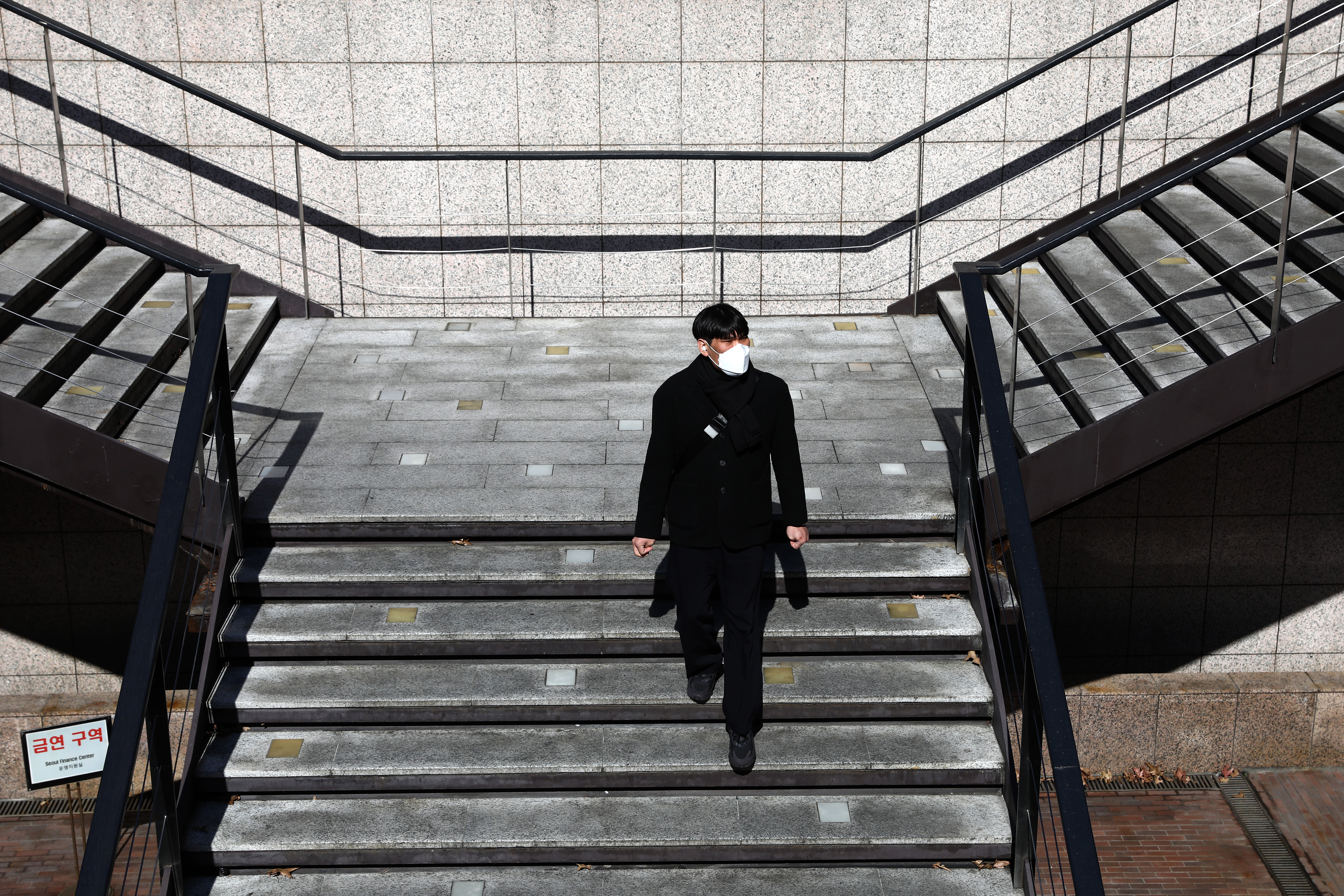 Dressed all in black, a white mask covering his face, a man descends an empty staircase, bathed in sunlight.