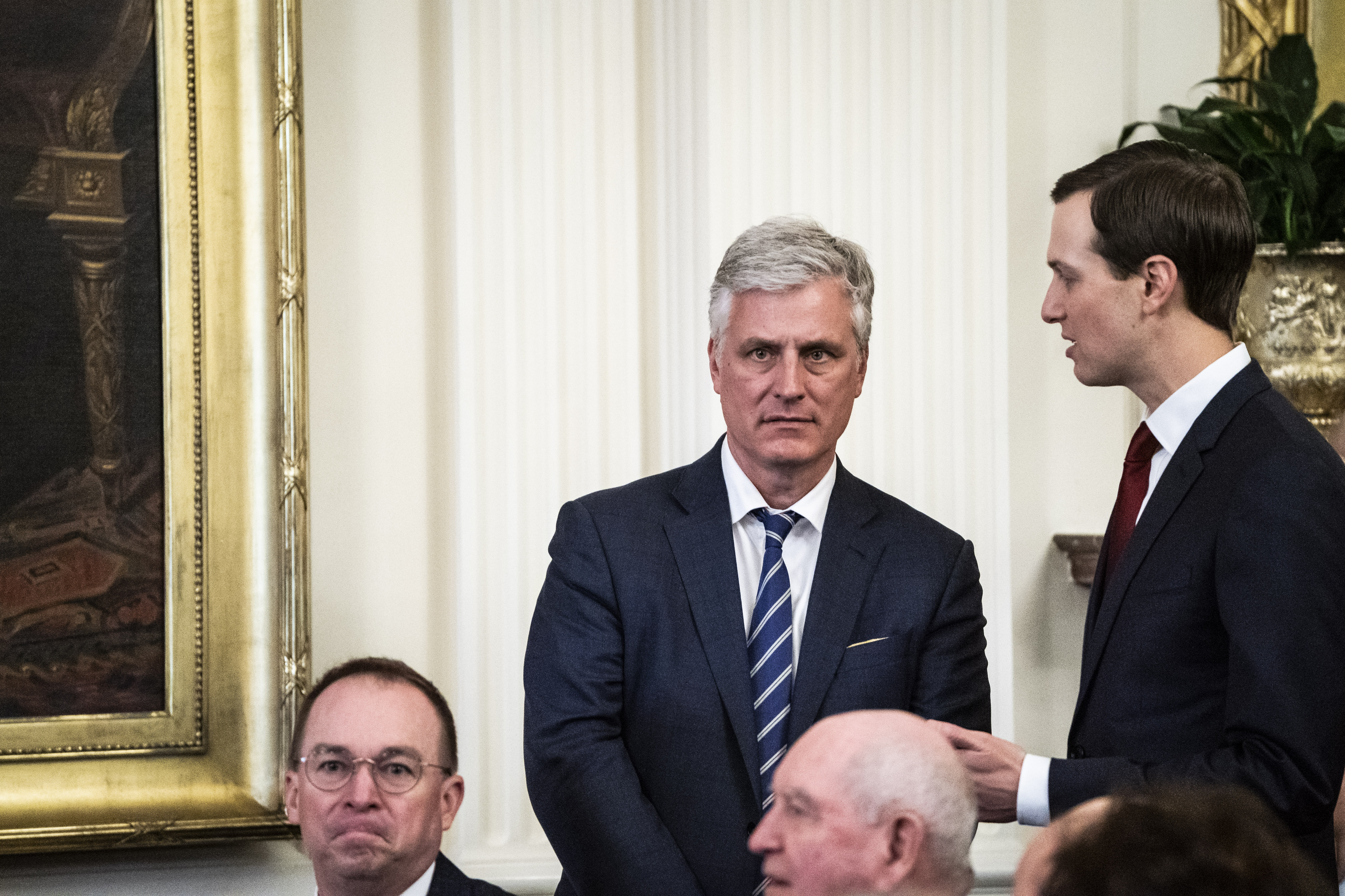 O'Brien stands sternly between Kushner and Mulvaney.