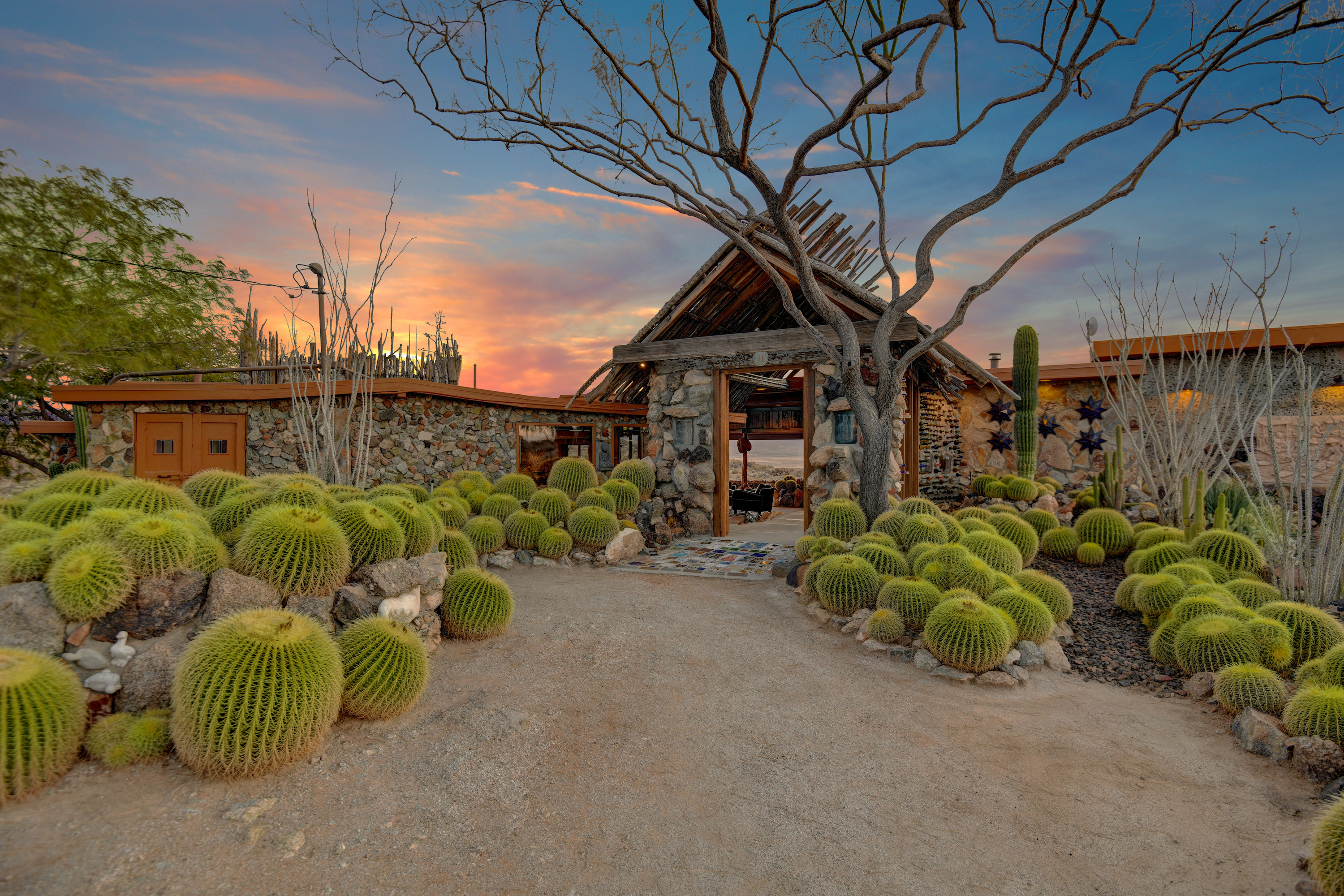 A wood and stone house sits in a landscaped desert garden with cacti and paths.