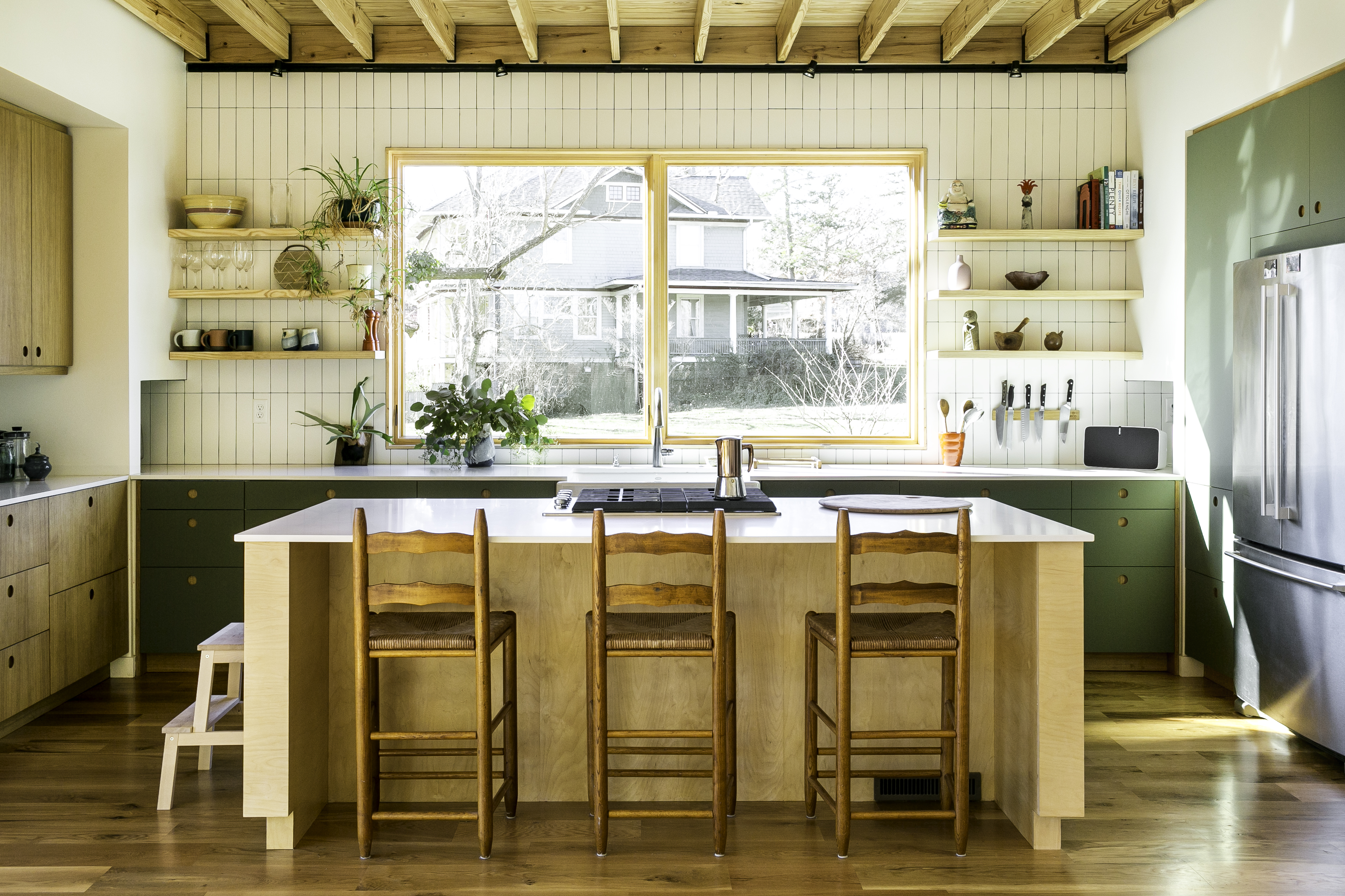 The kitchen, with a wall of tile backsplash in cream subway tile, open wooden shelving on either side of a large window above the sink, and white countertop, green cabinets. An island in the foreground has three wooden barstool chairs in front.