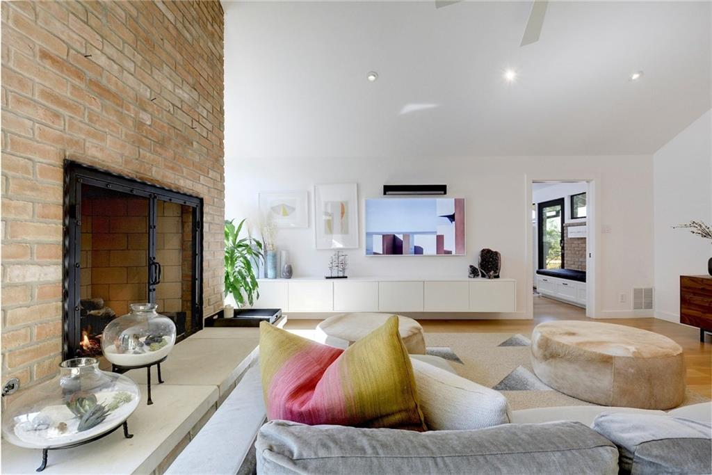 A photo of a living area with a brick fireplace with a floor-to-ceiling chimney on the left. There's a L-shaped couch in the foreground and modern credenza-type cabinet against the opposite wall under a mirror. There's a doorway to another room on the opposite wall on the right corner.