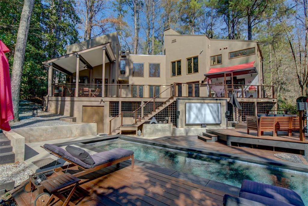 A large brown home with a pool and movie screen and many chairs.