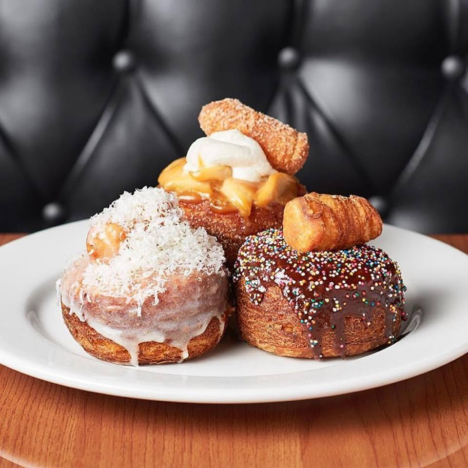 Three very large, multi-layered doughnuts with different toppings
