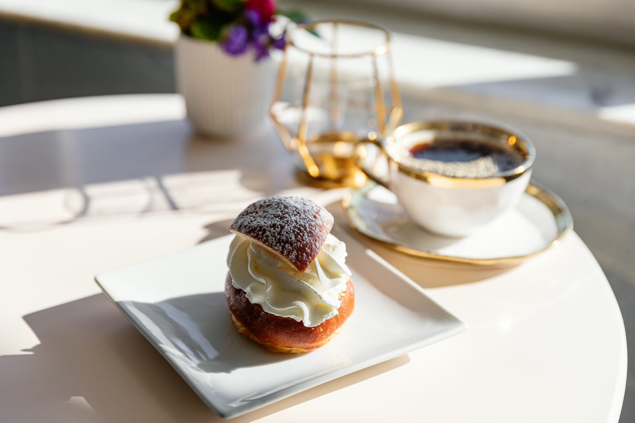 A bun on a white plate is filled with whipped cream and sits beside a cup of coffee in the sun.