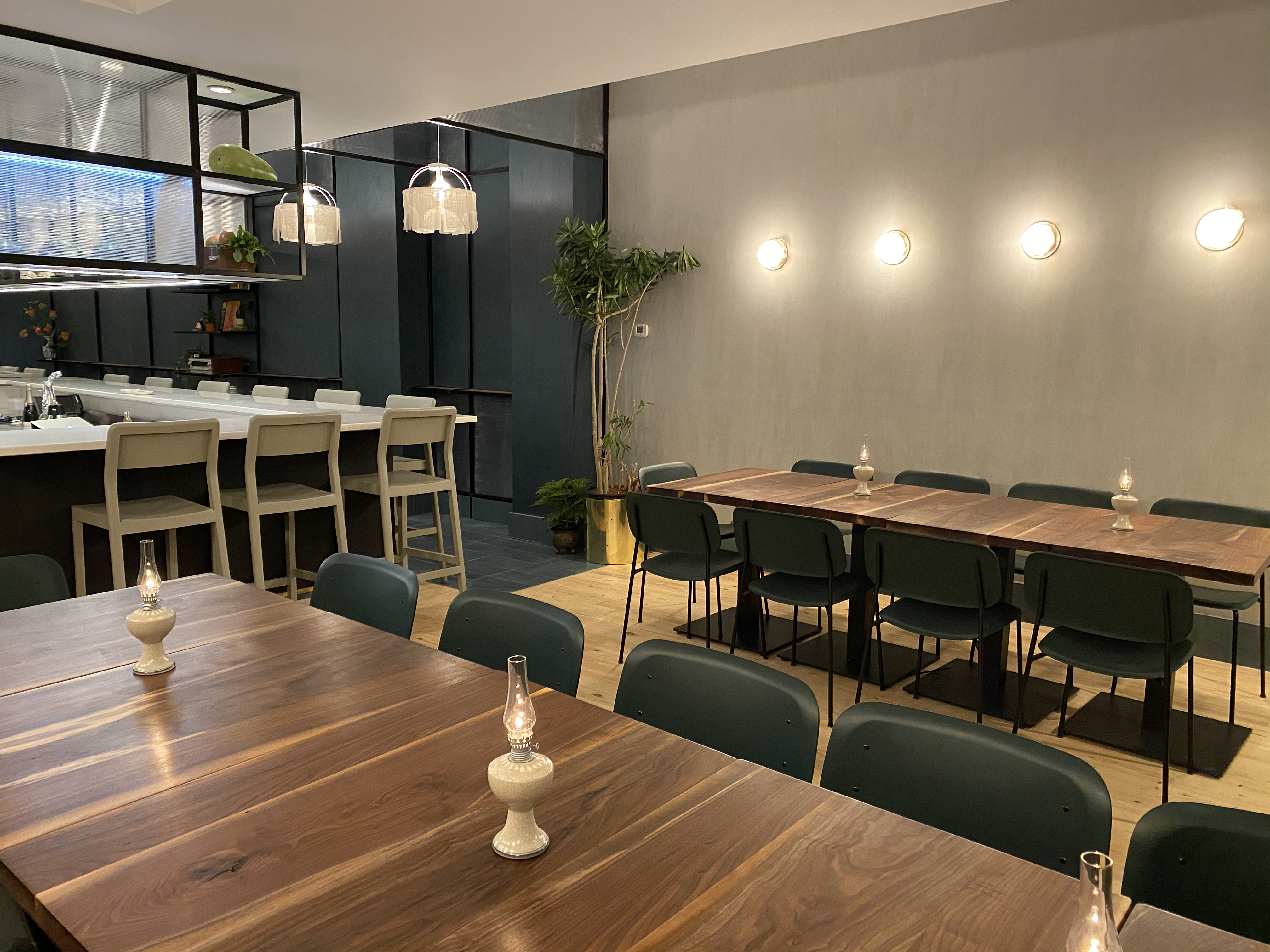 Two wooden tables and a bar with white seats. There are small lamps on each table and exposed bulbs on the wall.