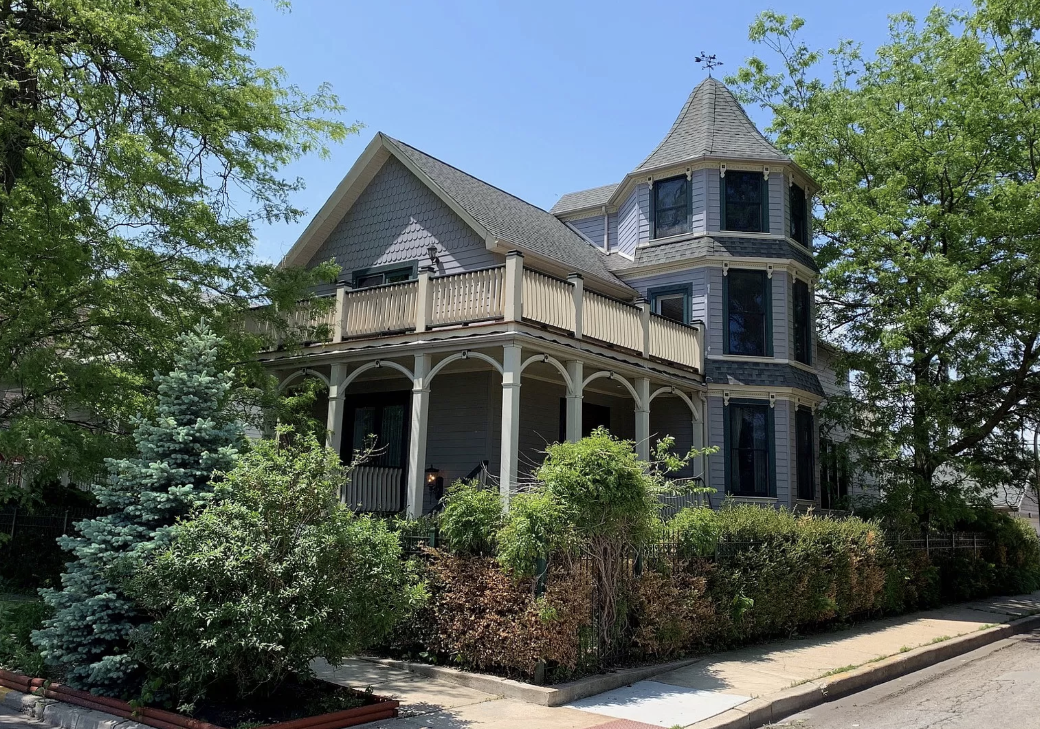 A home with Victorian era details like a front porch with white banisters, a turret, and purple siding. There is landscaping all around the front yard.