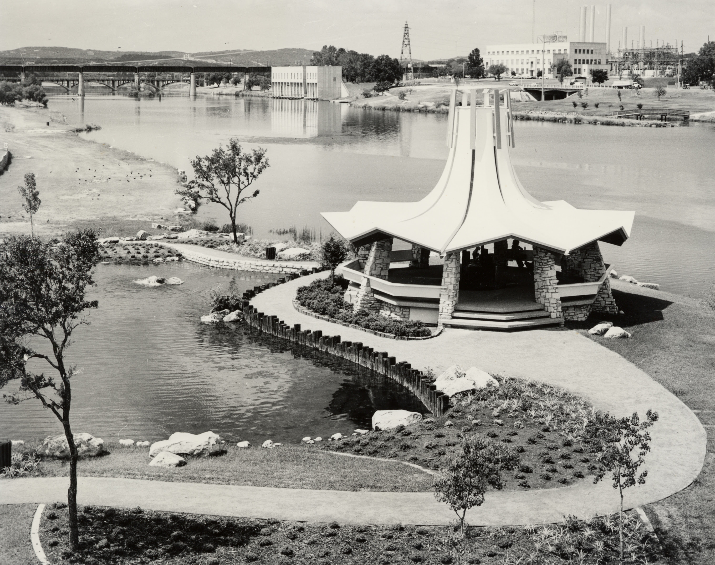 A black and white photo of a gazebo on a jetty-type land mass with a river behind it. The building has a zigzagged roof and slopes dramatically upward in a conical shape. The other shore of the lake has a few buildings on it and is in the background, along with two bridges in the distance.