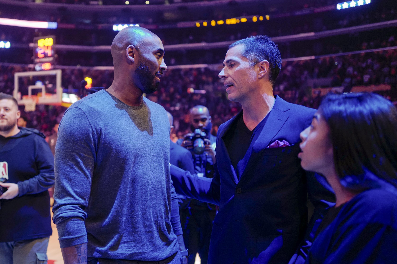 Former Los Angeles Lakers Kobe Bryant talks with Rob Pelinka during an NBA basketball game between Los Angeles Lakers and Atlanta Hawks, Sunday, Nov. 17, 2019, in Los Angeles. The Lakers won 122-101. (AP Photo/Ringo H.W. Chiu)