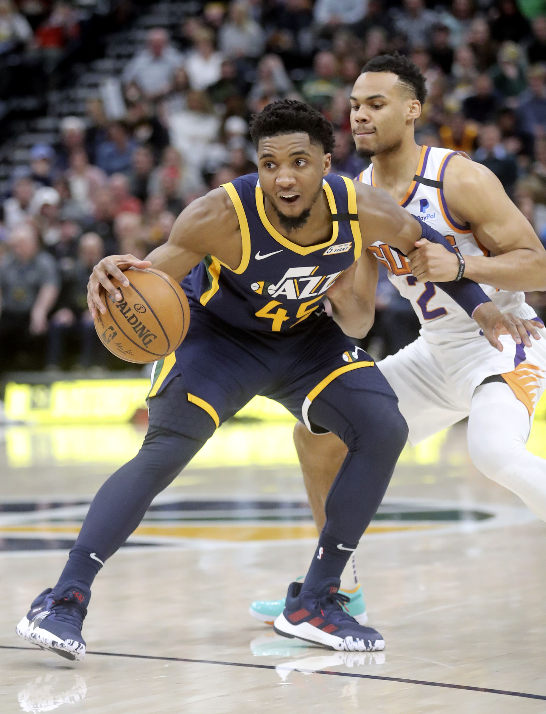 Utah Jazz guard Donovan Mitchell (45) dribbles around Phoenix Suns forward Elie Okobo (2) during an NBA game at the Vivint Smart Home Arena in Salt Lake City on Monday, Feb. 24, 2020.