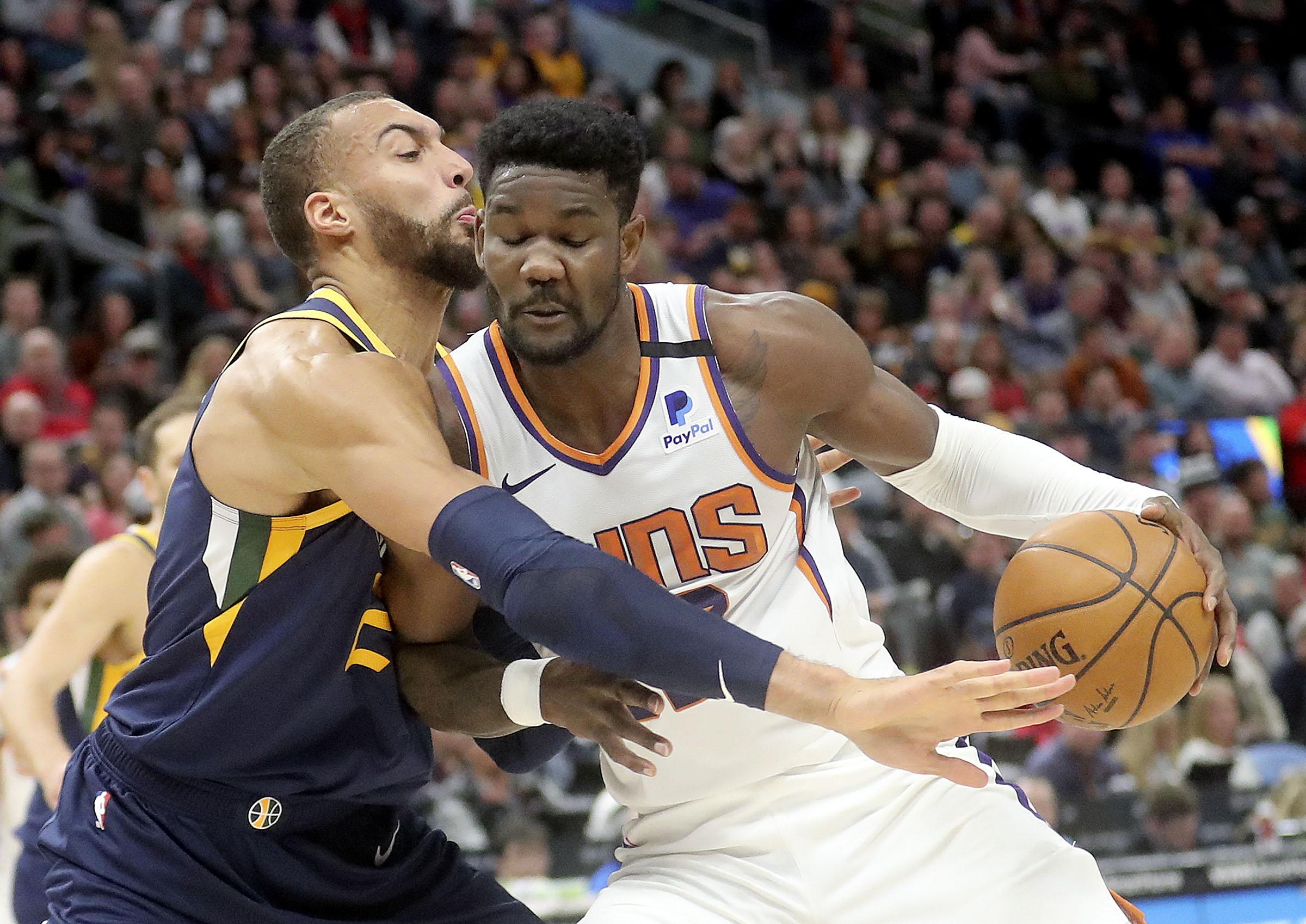 Utah Jazz center Rudy Gobert (27) guards Phoenix Suns center Deandre Ayton (22) during an NBA game at the Vivint Smart Home Arena in Salt Lake City on Monday, Feb. 24, 2020.