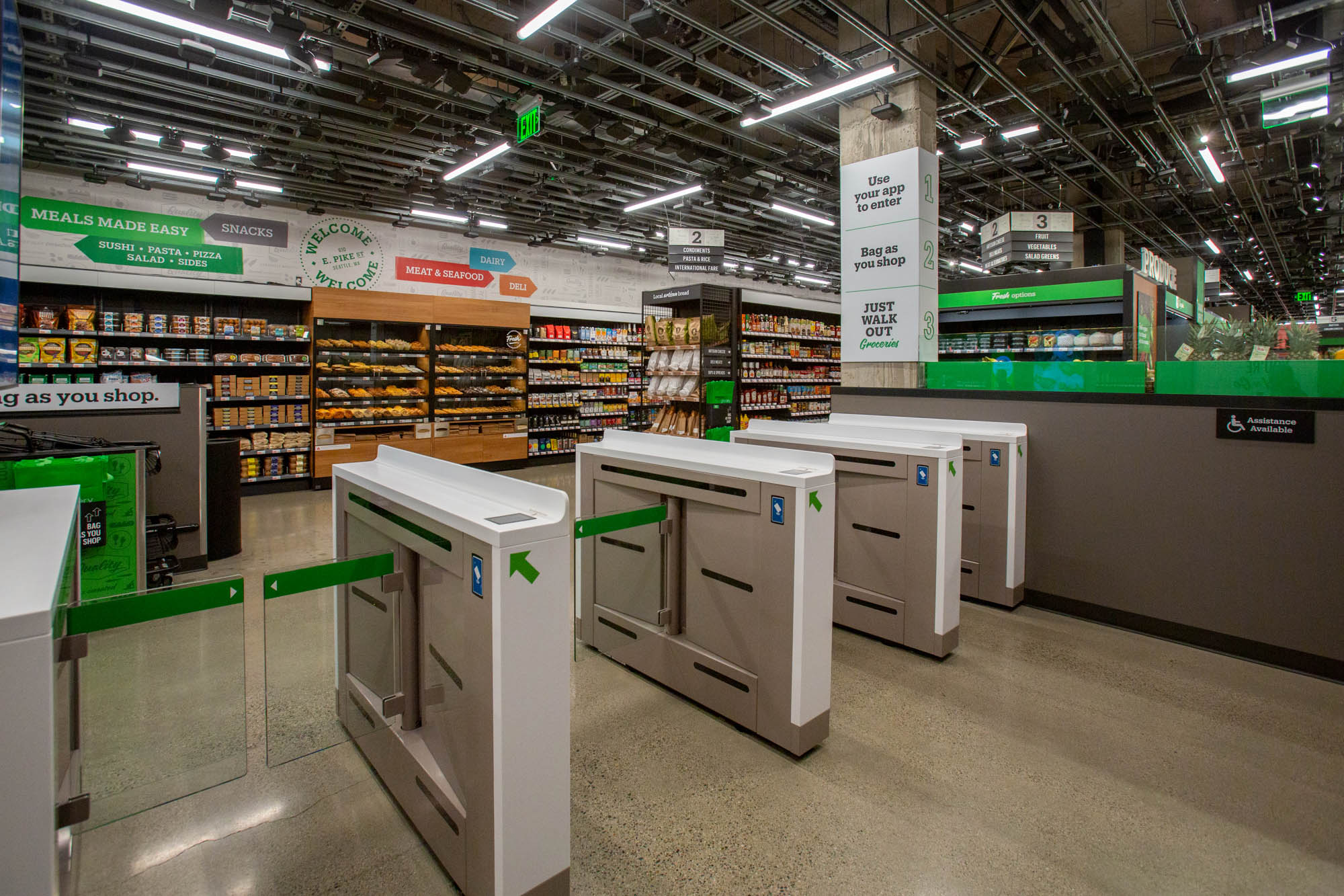 The interior of Amazon Go Grocery, with a cashierless exit and green accents throughout the store.