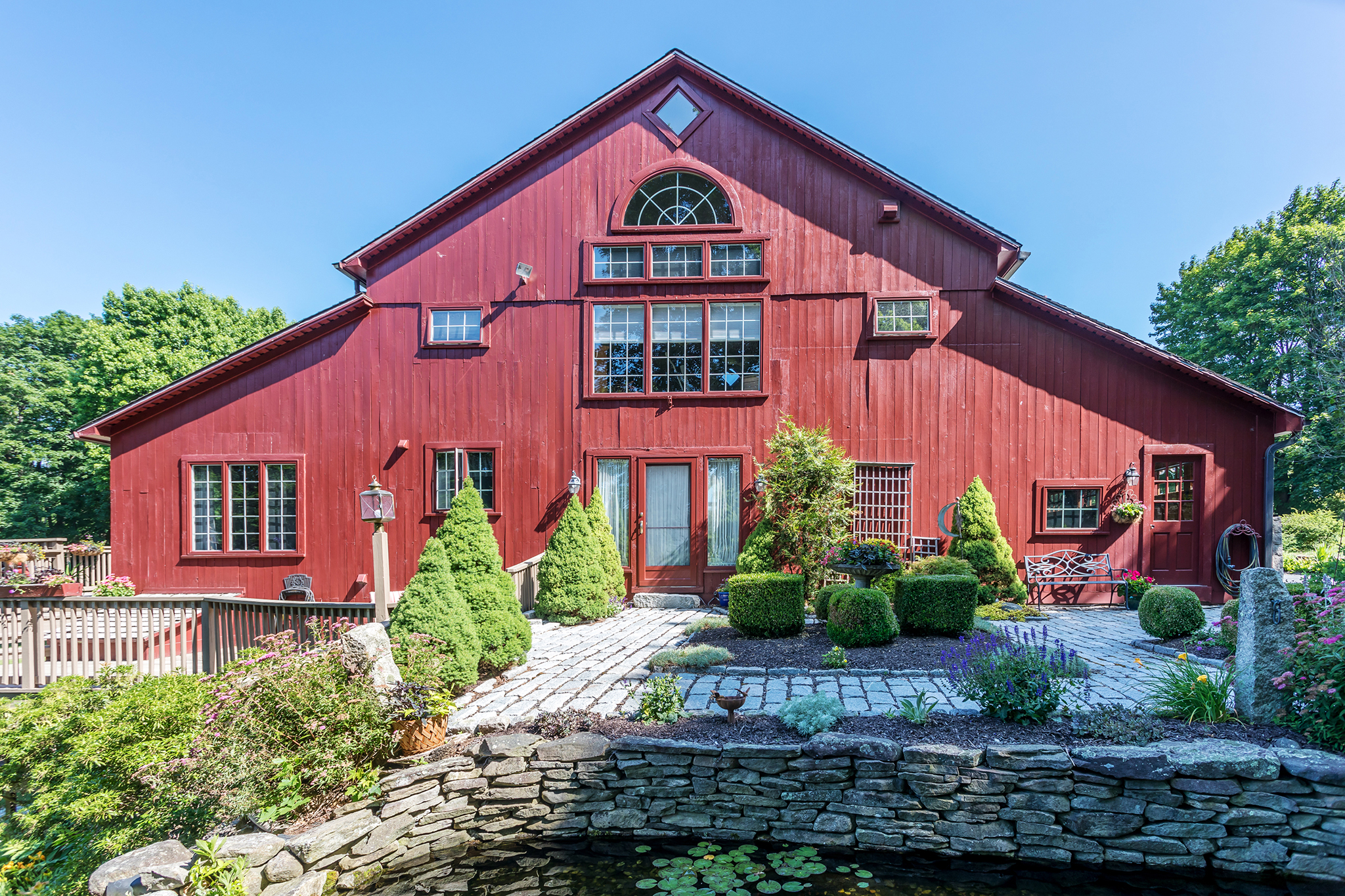 An exterior view of a large red barn converted into a house with bushes and landscaping all around.