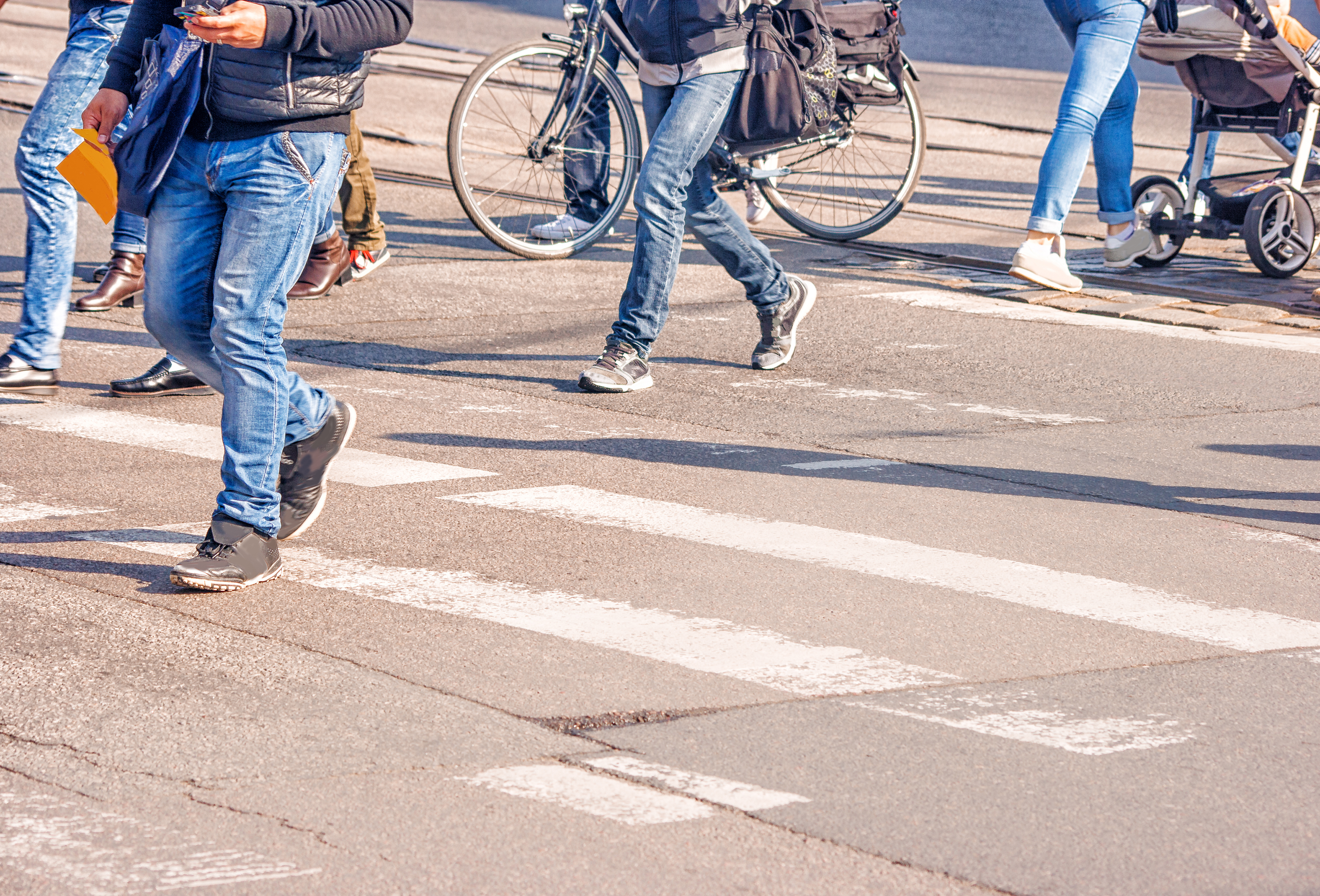 People crossing at a crosswalk show a variety of transportation modes, including walking, biking, and pushing a stroller.