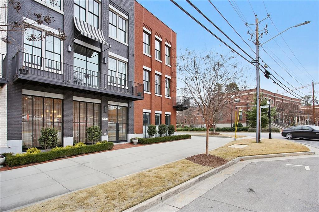 A row of townhomes in black and red brick with balconies and many windows, with grass in front in small strips.