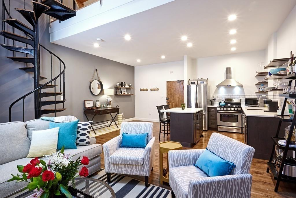 An open living room-dining room with furniture, and it's next to an open kitchen, and there's a spiral staircase featuring prominently.