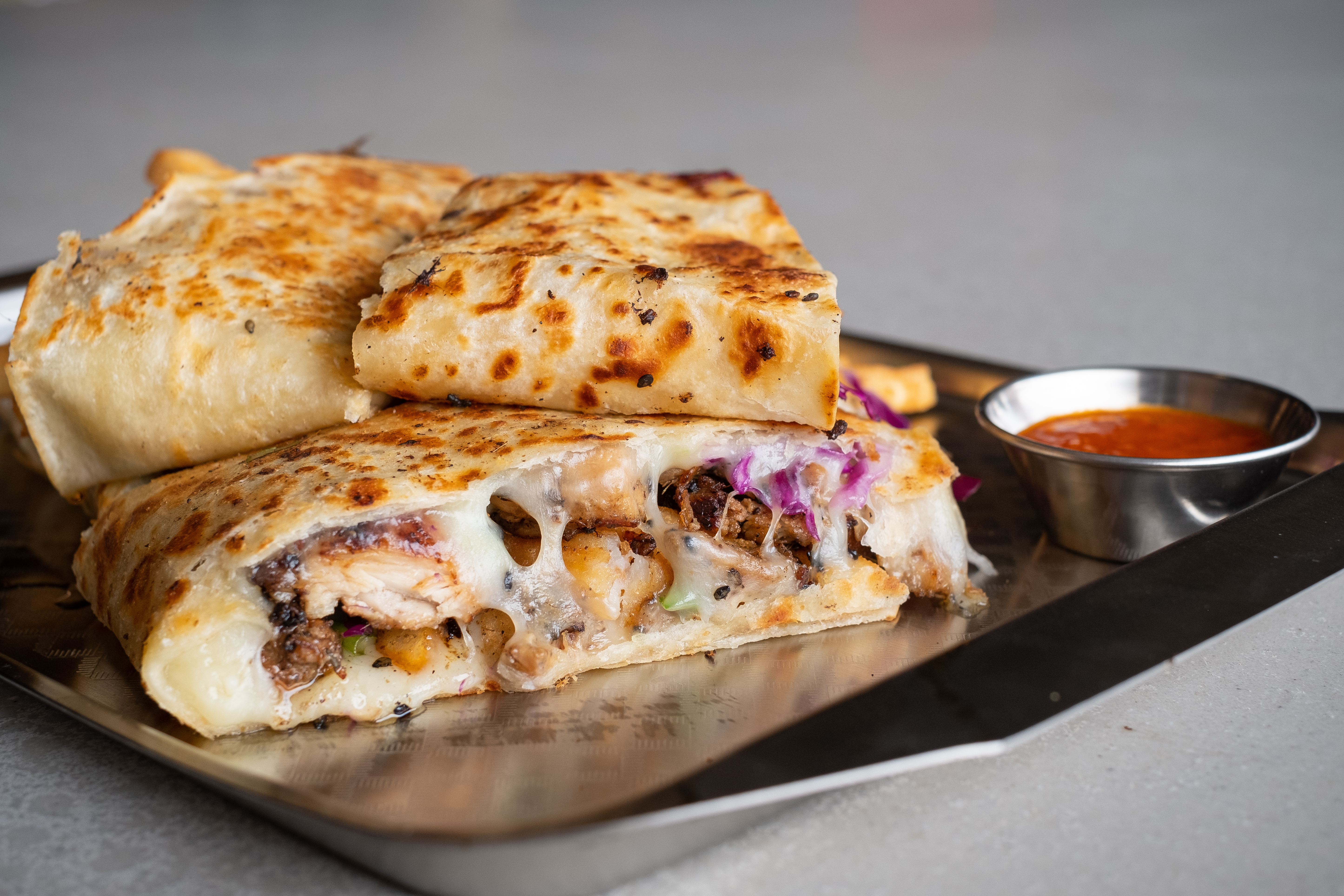 A giant quessadilla stuffed with goodies and gooey cheese