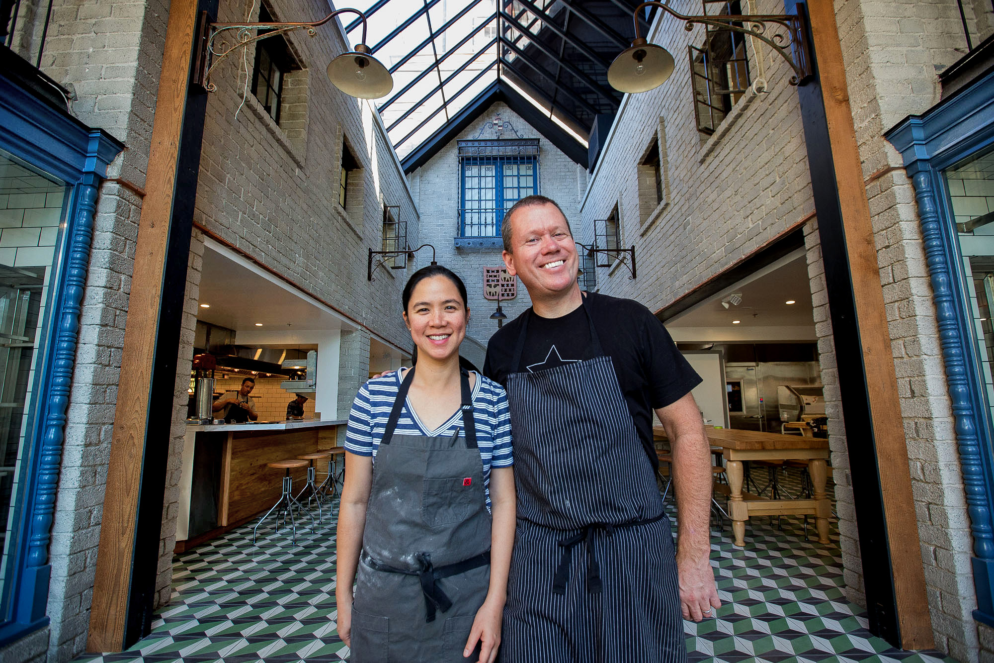 Republique's Walter and Margarita Manzke pose in denim aprons in front of their soaring atrium dining room.