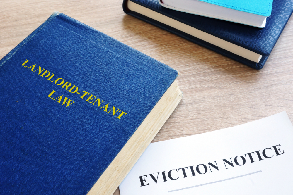 """A book with a blue cover reading """"landlord-tenant"""" law lying on a desk with a piece of paper that reads """"eviction notice."""""""