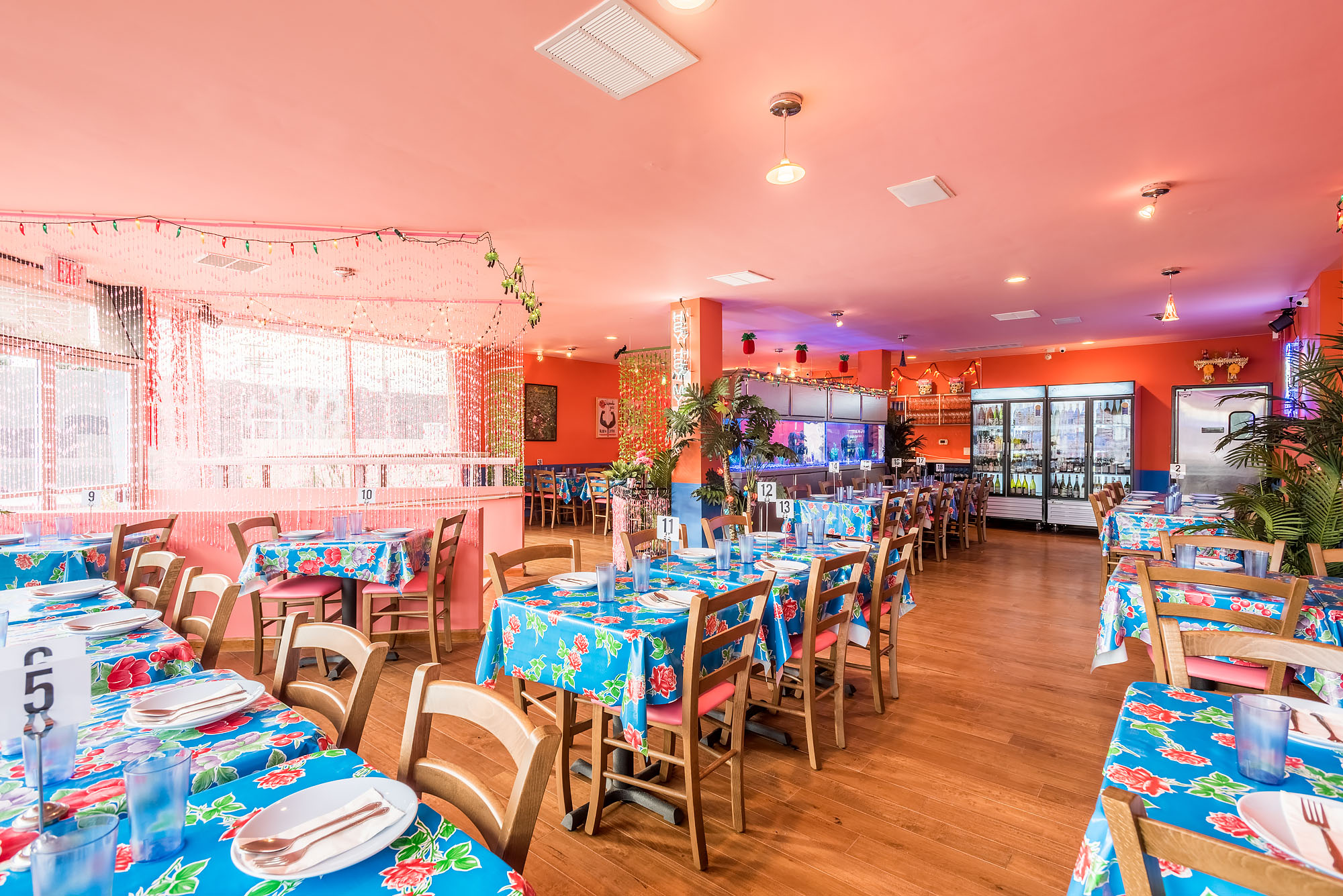 A dining room with tables covered in blue, floral oilcloth tablecloths