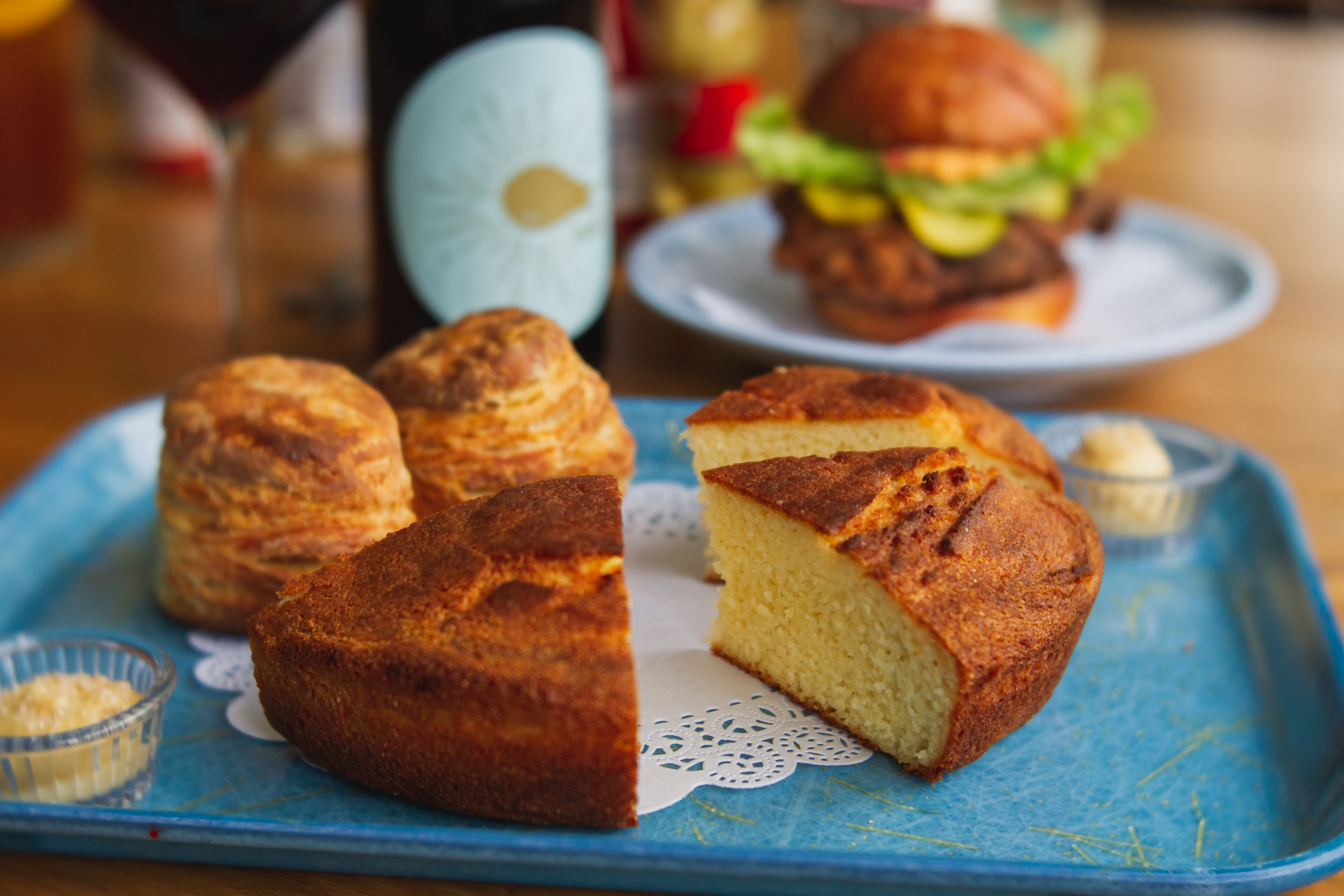 A loaf of cornbread sits on a doily on a blue tray, next to two biscuits and some sorghum butter. Behind it, a bottle of Yonder's brand wine and an Intimidator sandwich sit out of frame.