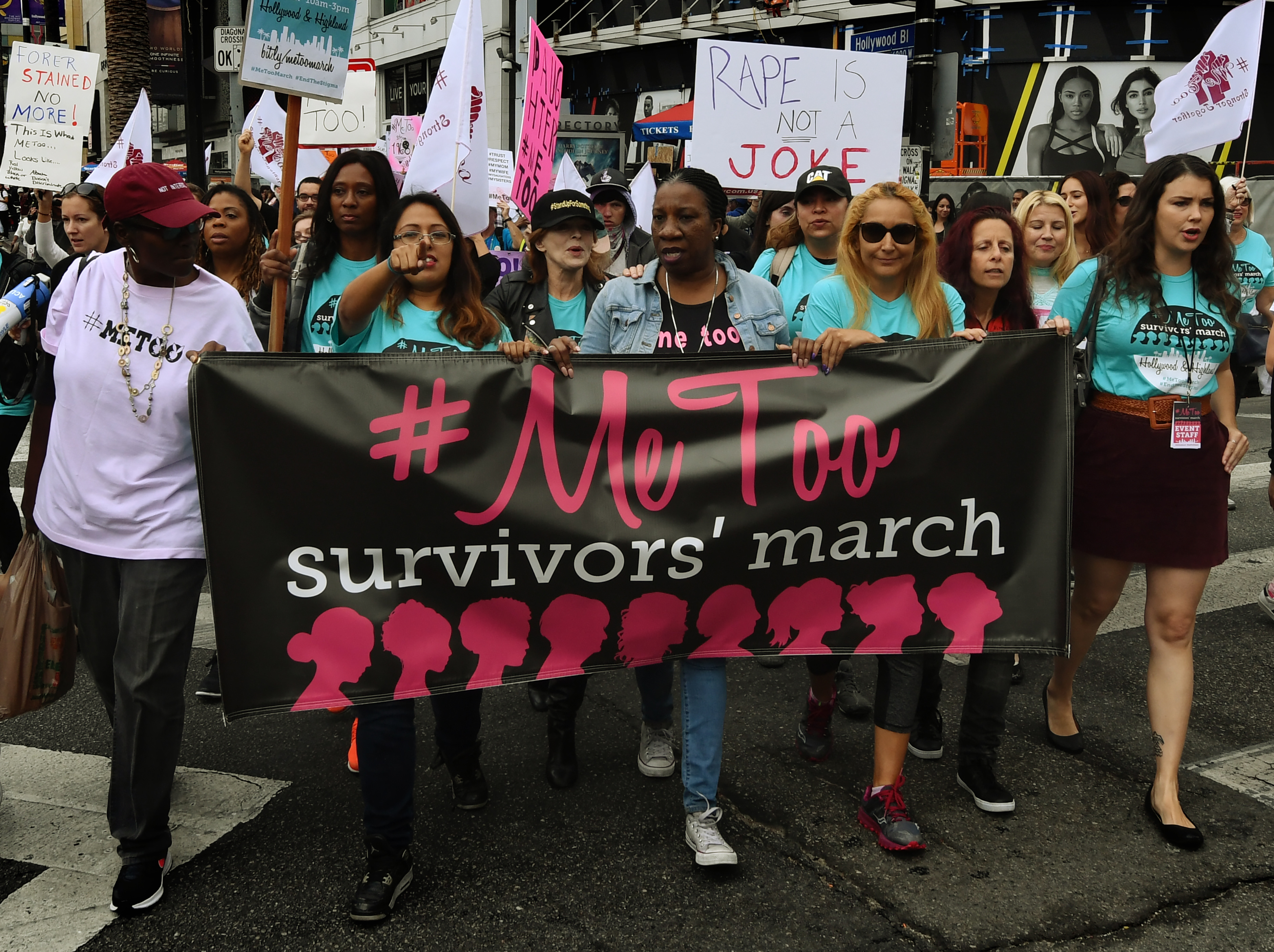"Activists marching in Hollywood hold a banner that reads, ""#MeToo survivors' march."""