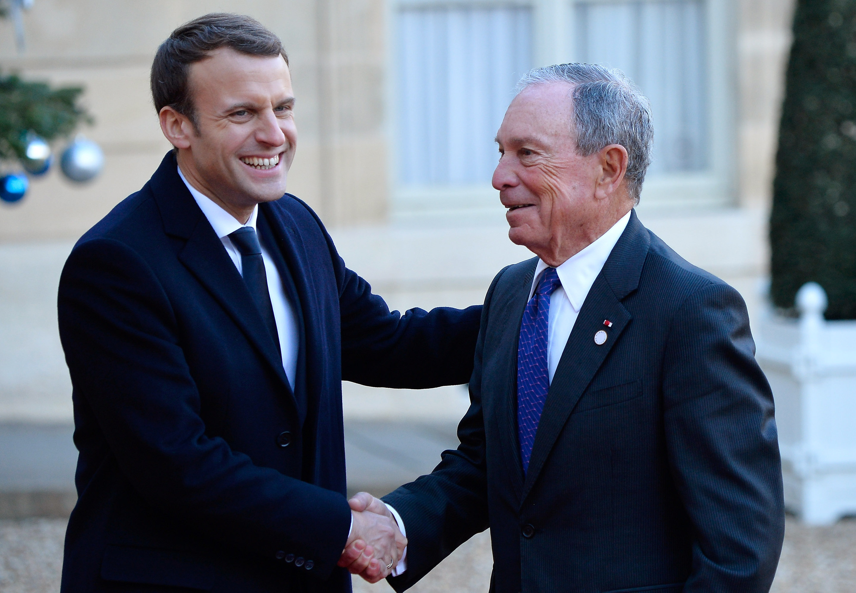 French President Emmanuel Macron and Mike Bloomberg shaking hands.