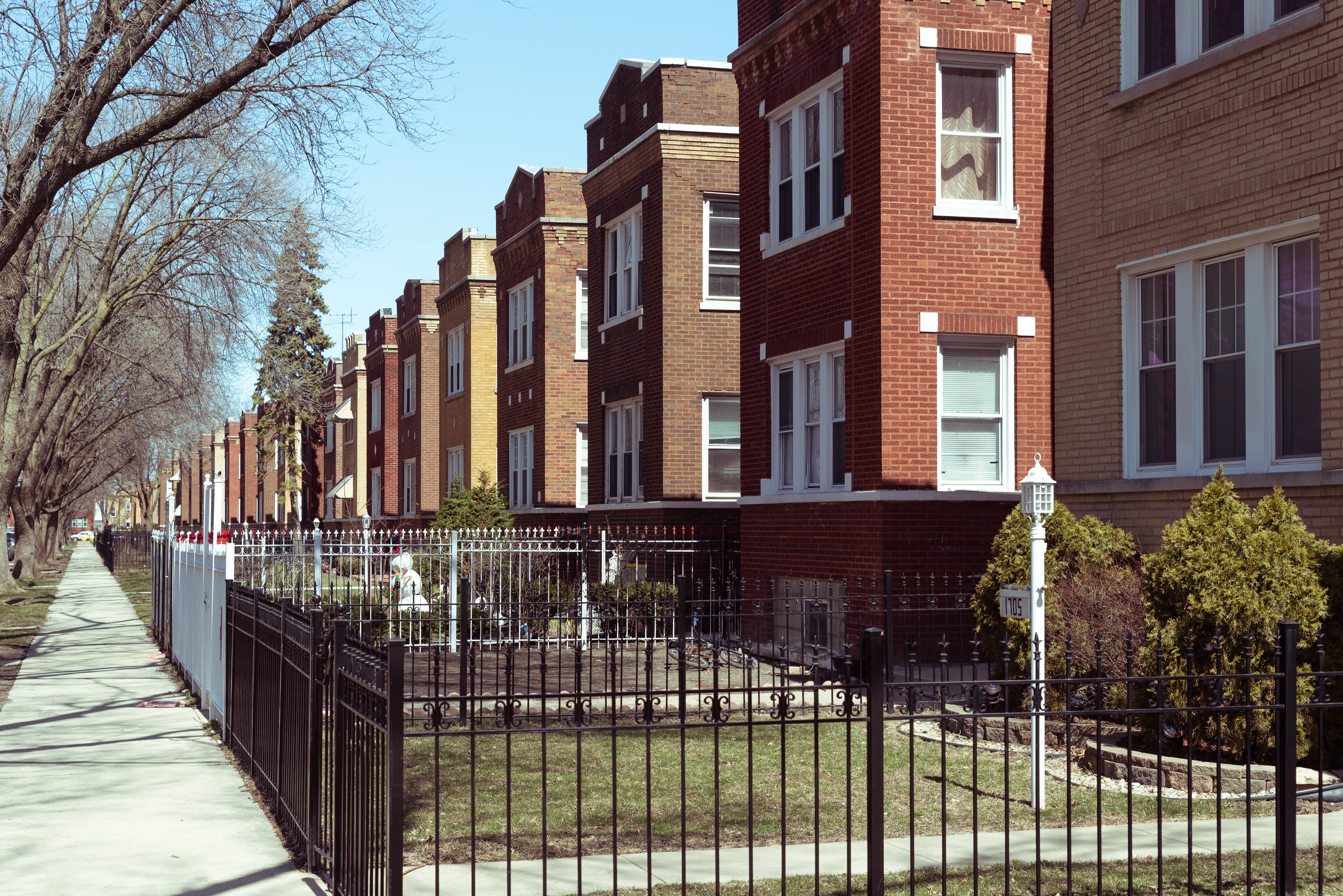 A row of brick residential buildings standing two and three stories high on a street with trees and grassy lawns.