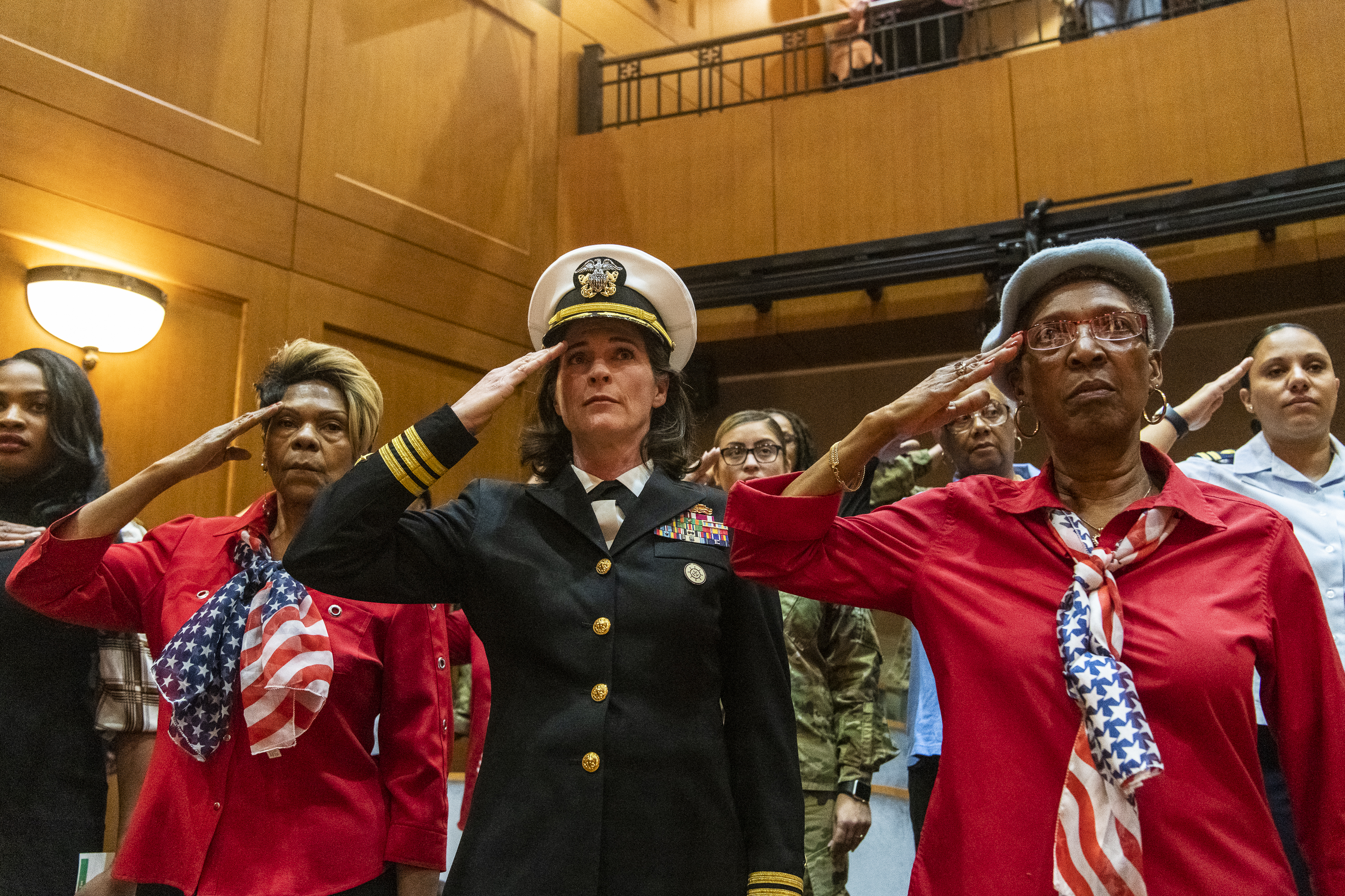 Women veterans of every branch of the U.S. military salute as the national anthem is sung at an auditorium at the Pritzker Military Museum and Library for the announcement of the first all women honor flight to Washington D.C. later this year.