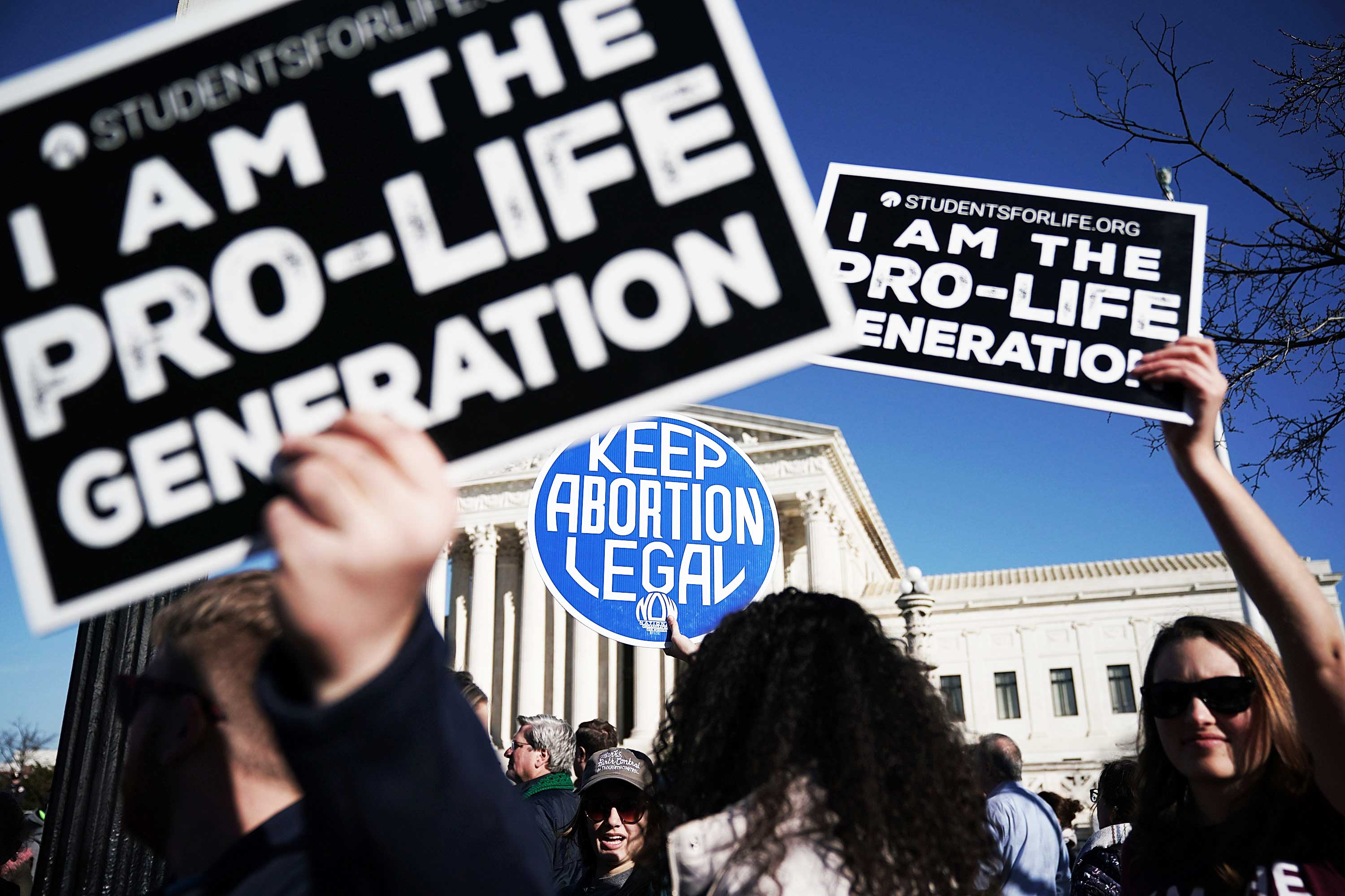 "Activists hold up competing signs at a protest in front of the Supreme Court: ""I am the pro-life generation"" and ""Keep abortion legal."""