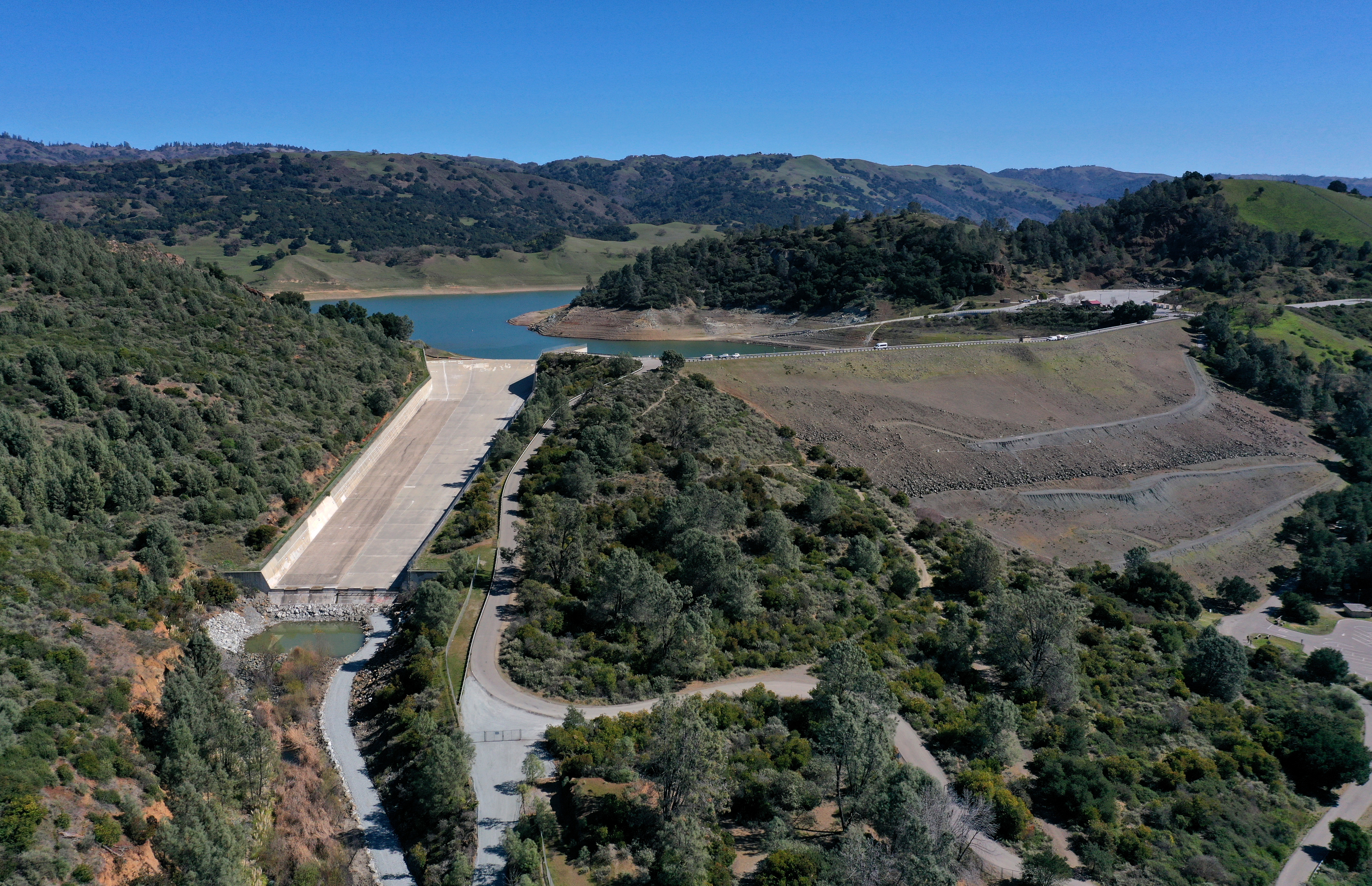 A view of the dam at Anderson Reservoir, an earthen dam with a placid looking lake behind it and a tree-lined hillside in front.