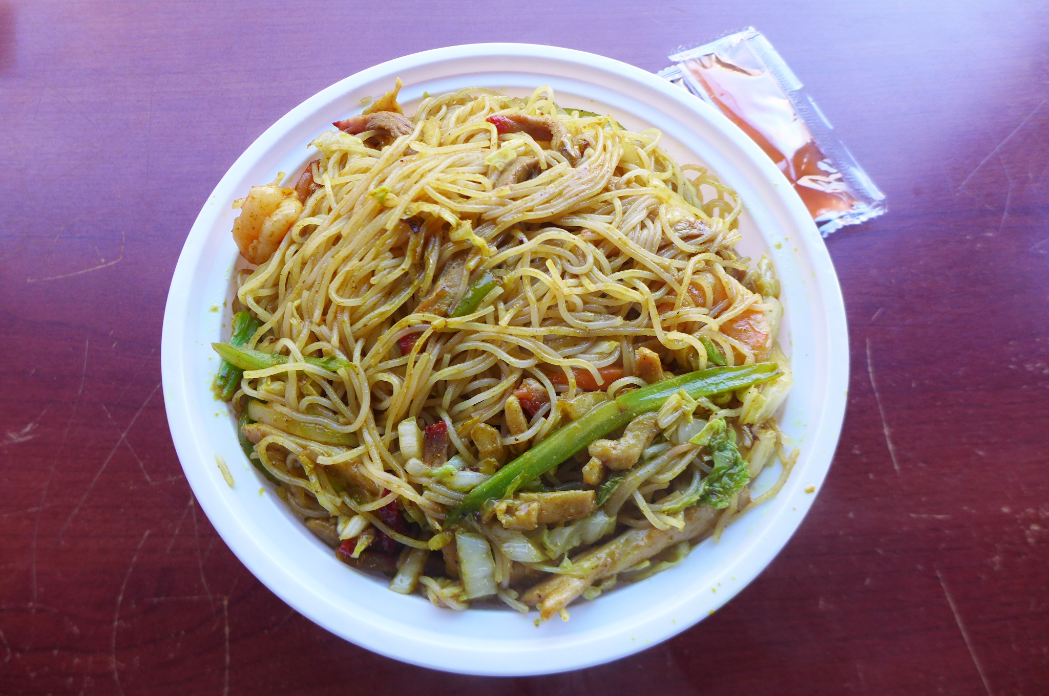 A white plastic bowl of Chinese noodles.