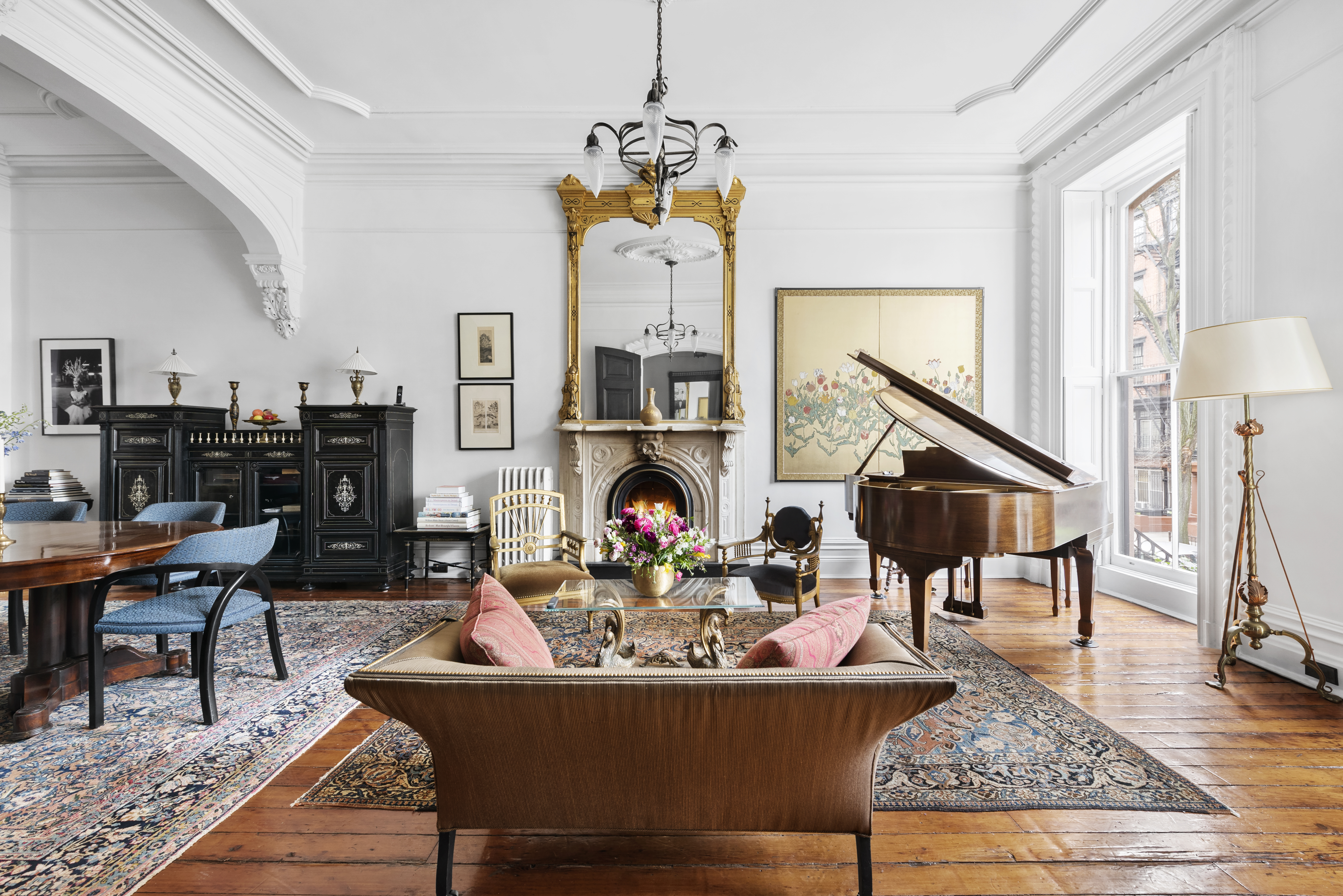 A living area with crown moldings, a wood-burning fireplace, a piano, and hardwood floors.