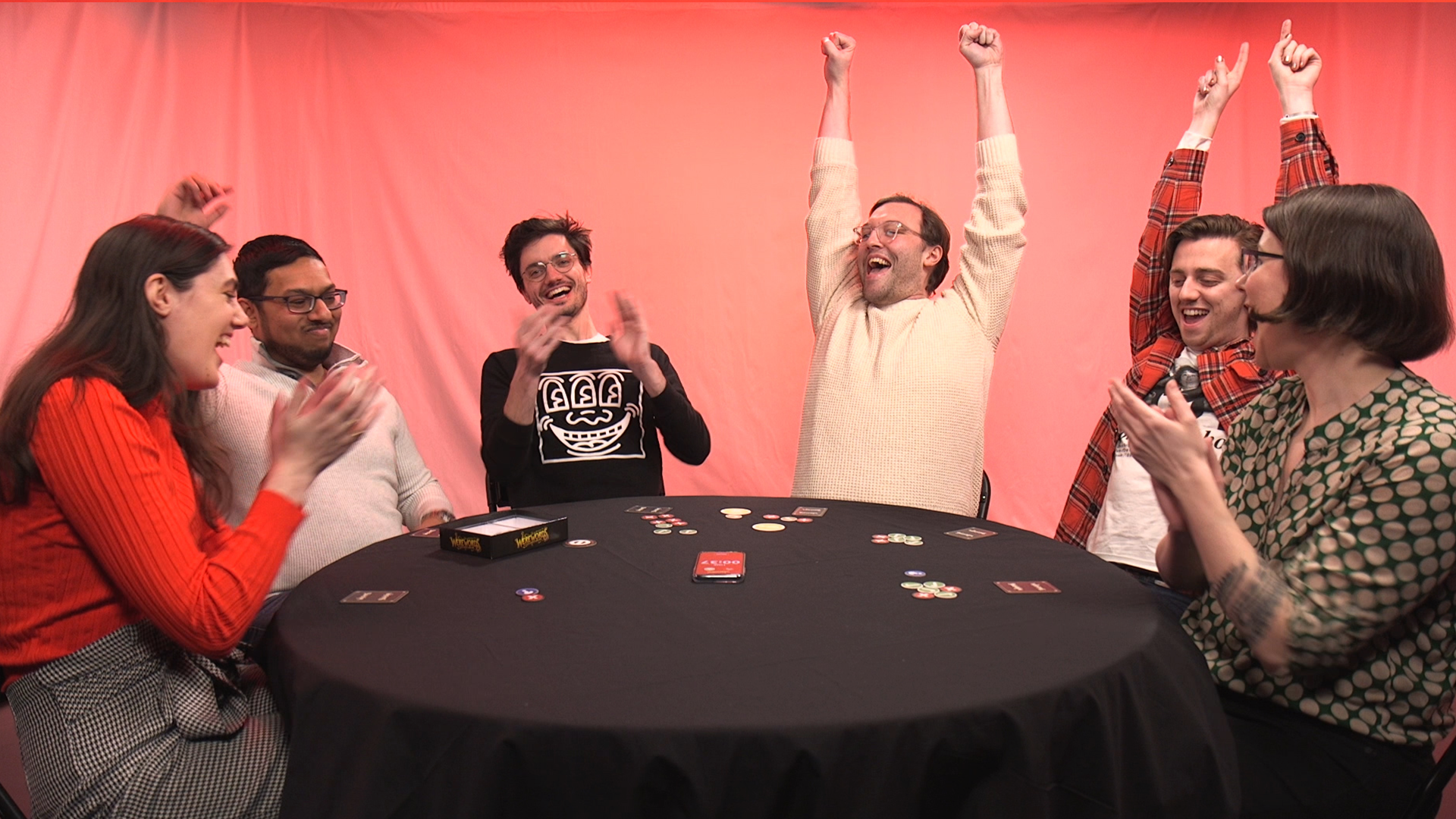 a group of six people sitting around a table playing a board game are cheering in celebration, some raising their arms over their heads in victory while others applaud.