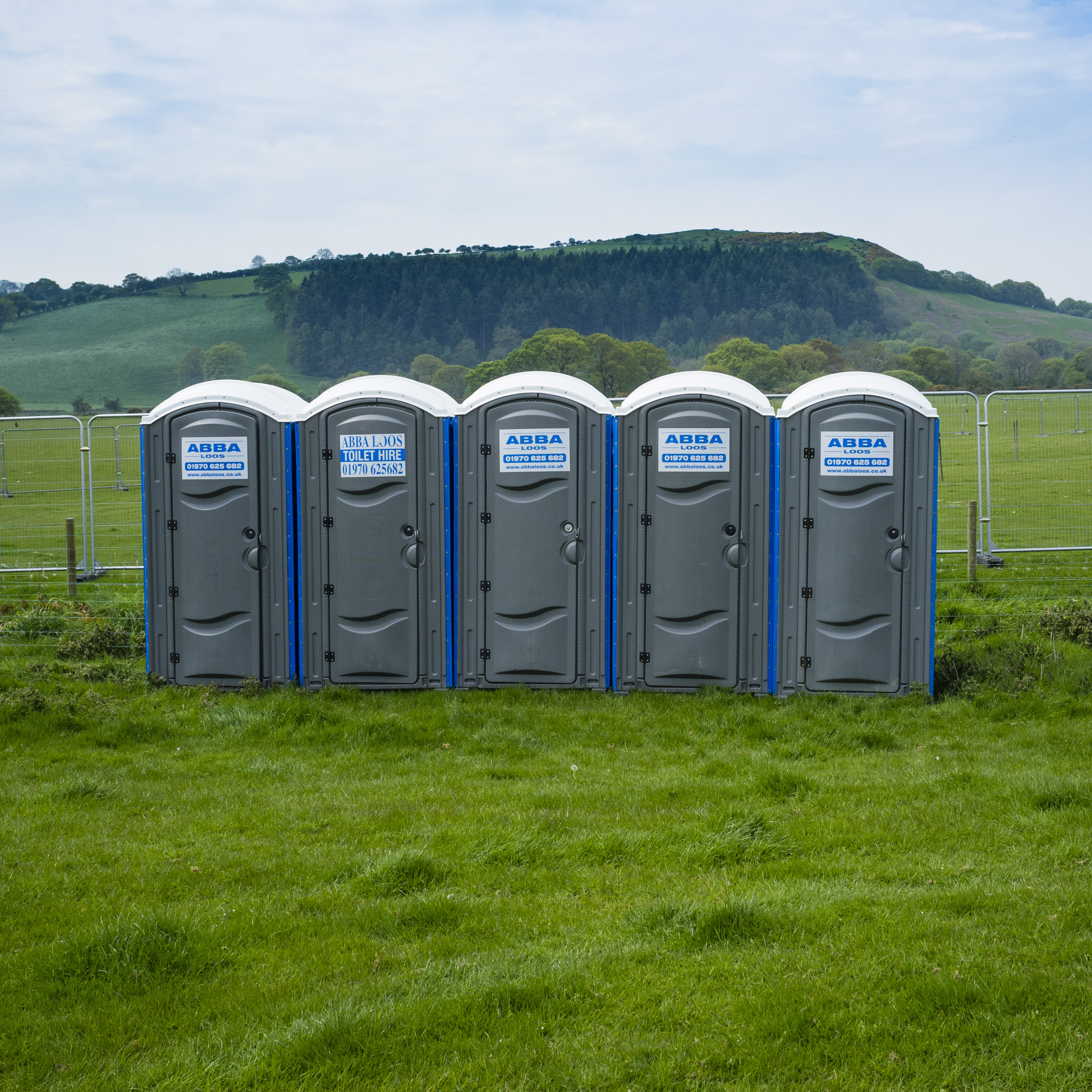 A row of 5 five portable toilets at a festival, UK
