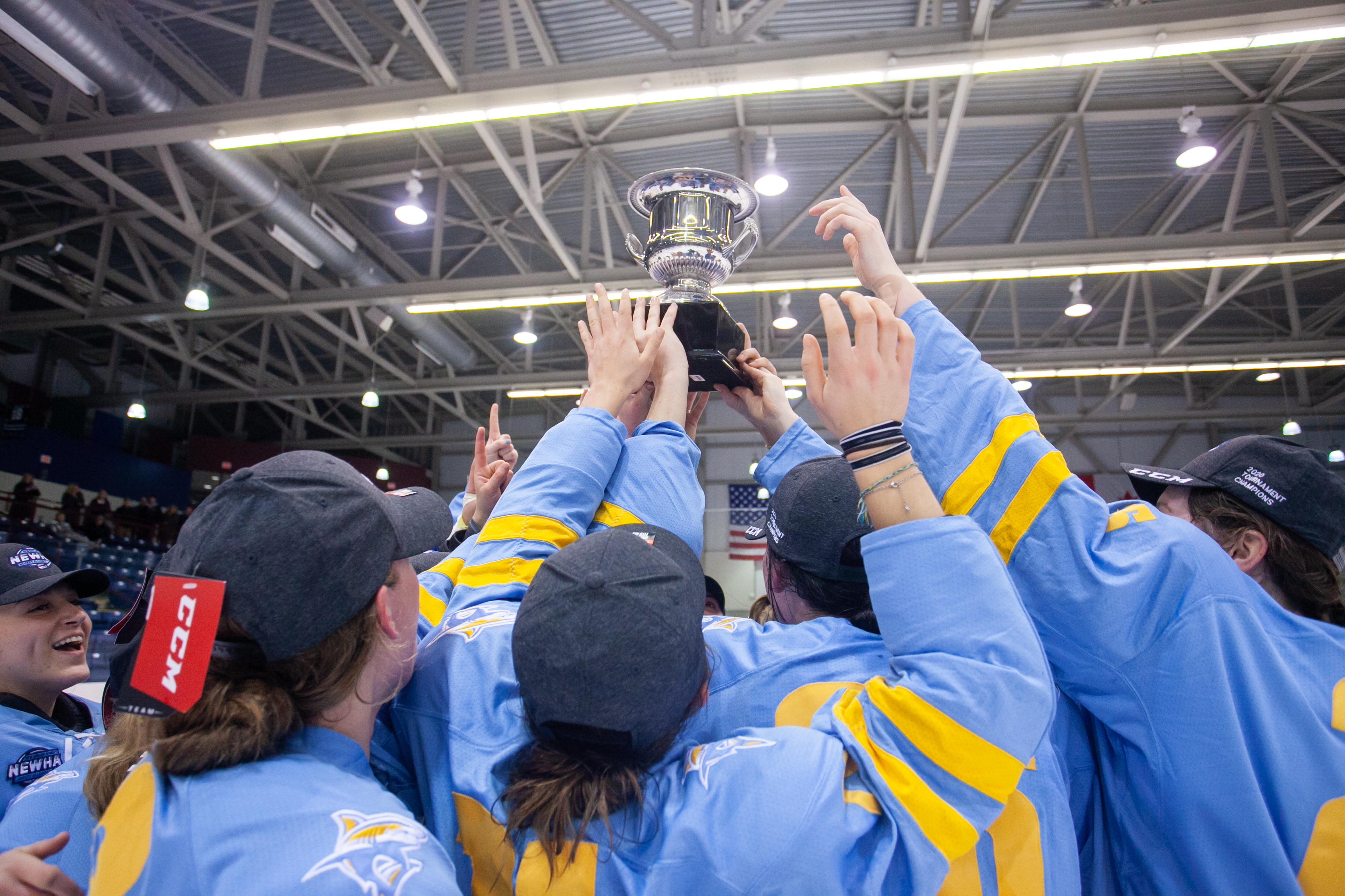 The LIU Sharks celebrate their NEWHA championship with the trophy held high.