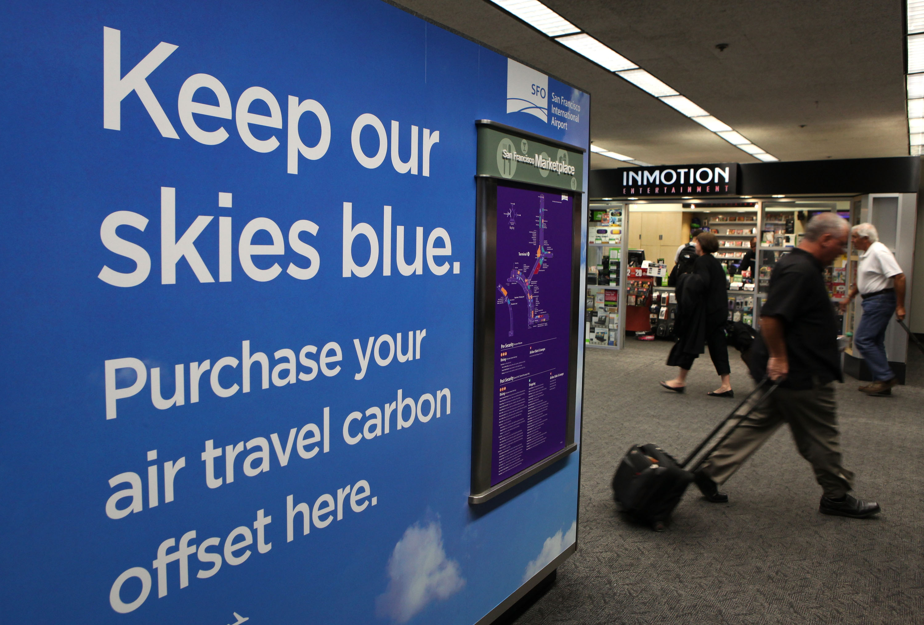 A traveler walks by a sign for the new Climate Passport carbon offset kiosk September 29, 2009 at San Francisco International Airport in San Francisco, California.