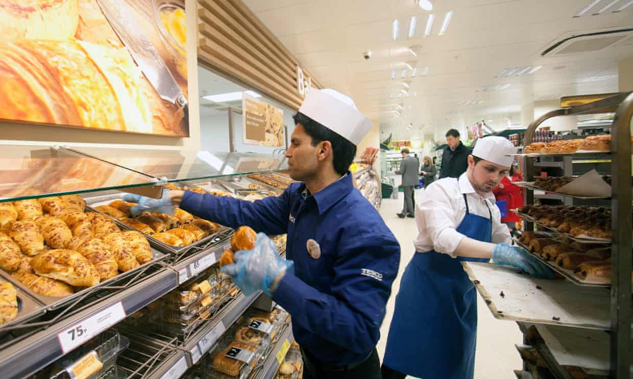Staff load pastries on to racks at a Tesco bakery