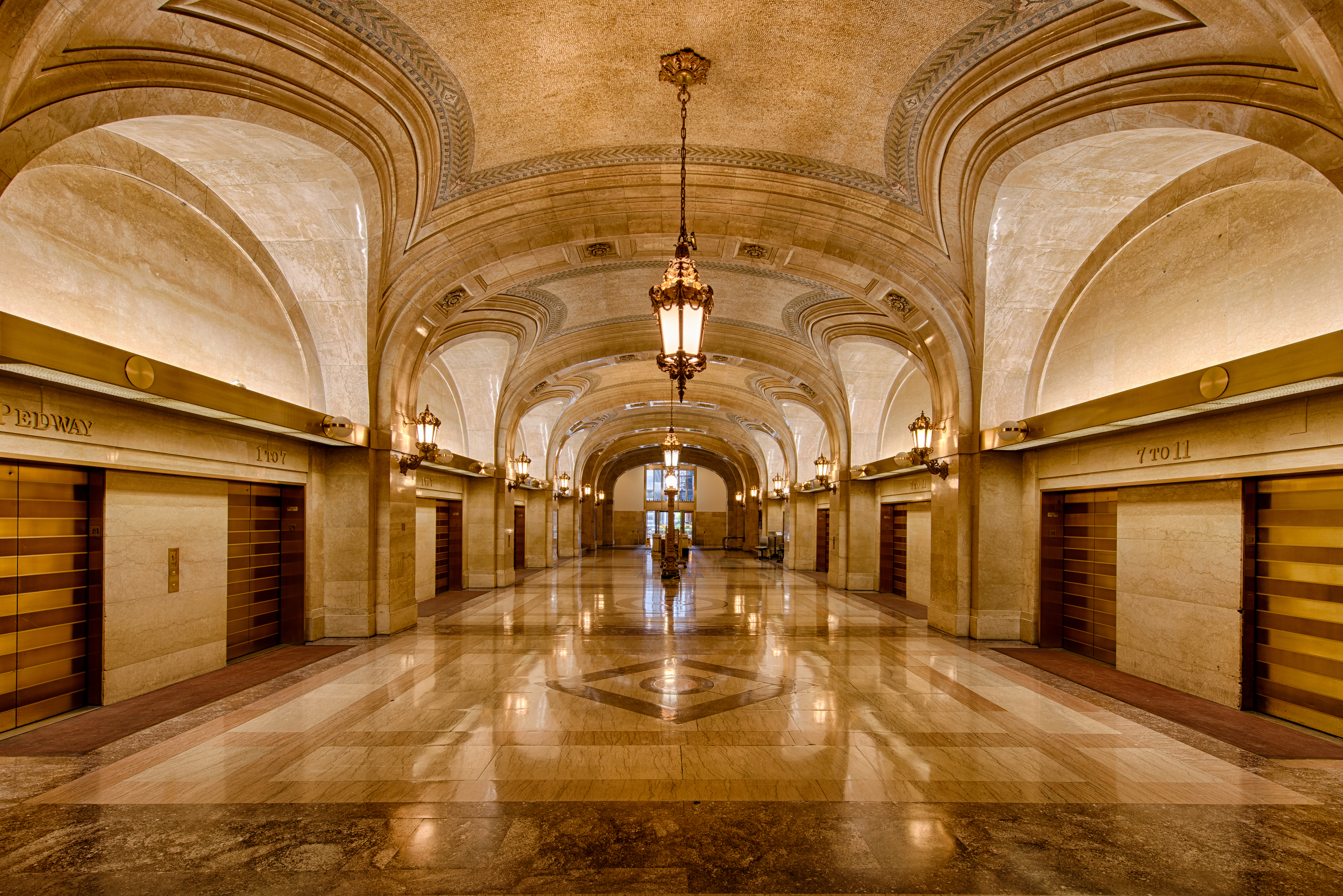 A marble-clad hall with lantern chandeliers, gold elevators, and detailed floors.