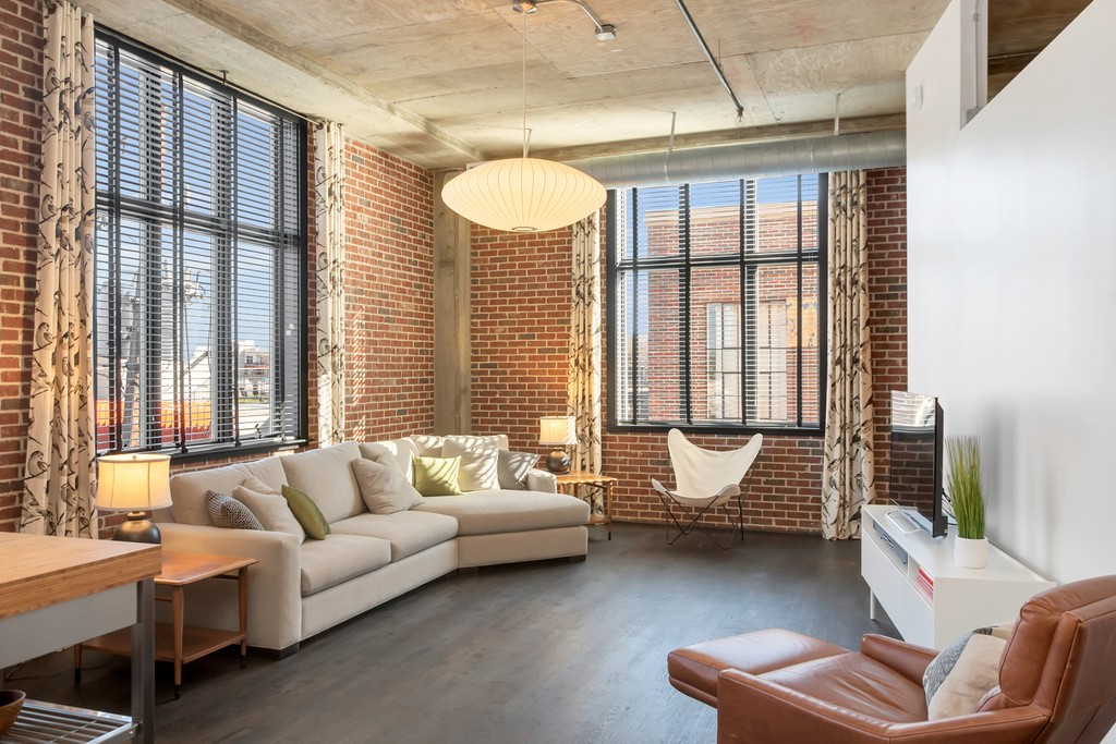 A condo with brick walls and huge industrial windows and a gray couch.