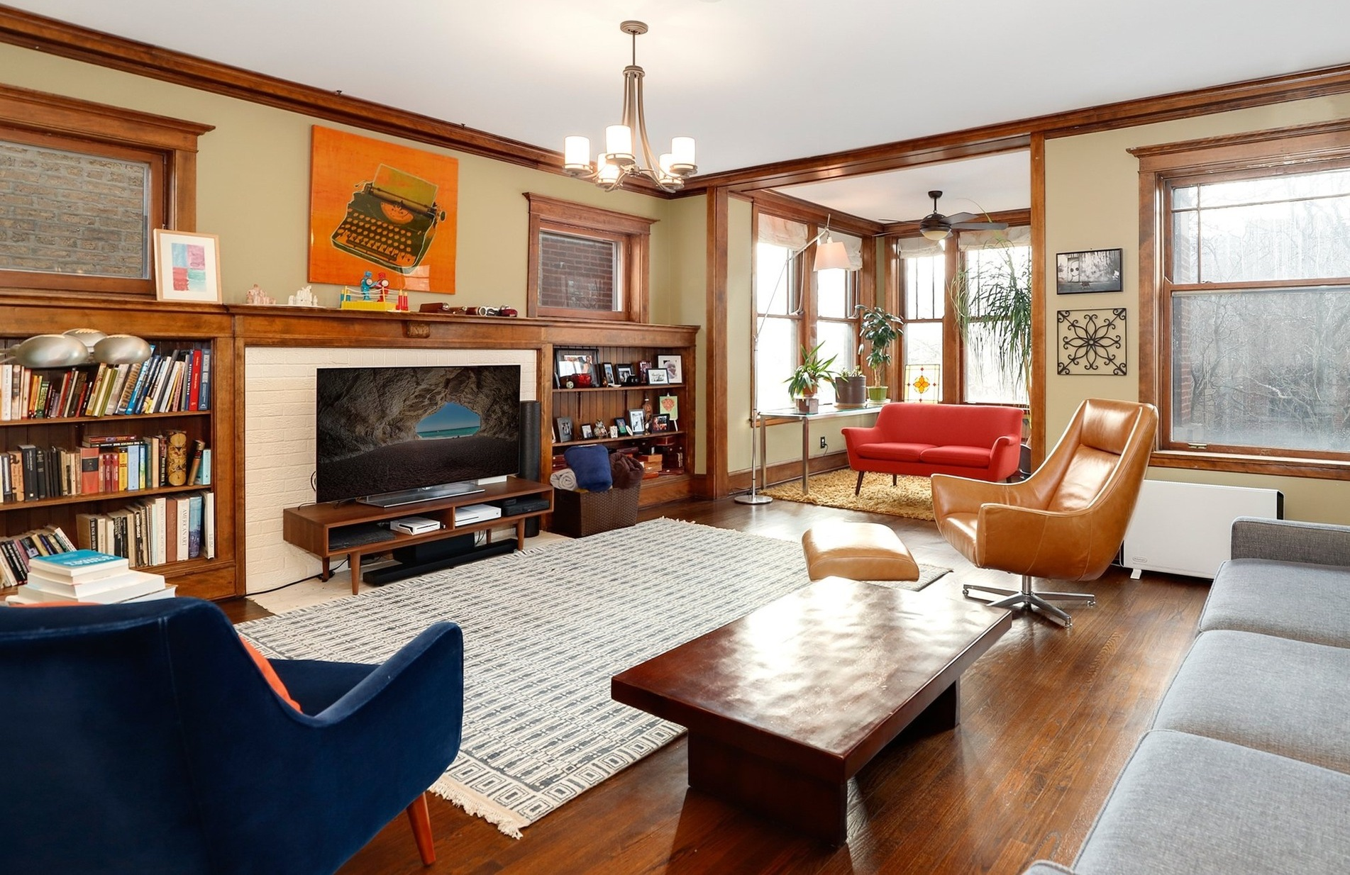 A living room with hardwood floors, a decorative brick fireplace flanked by built-in shelves, an area rug, coffee table, velvet chair, and sofa.