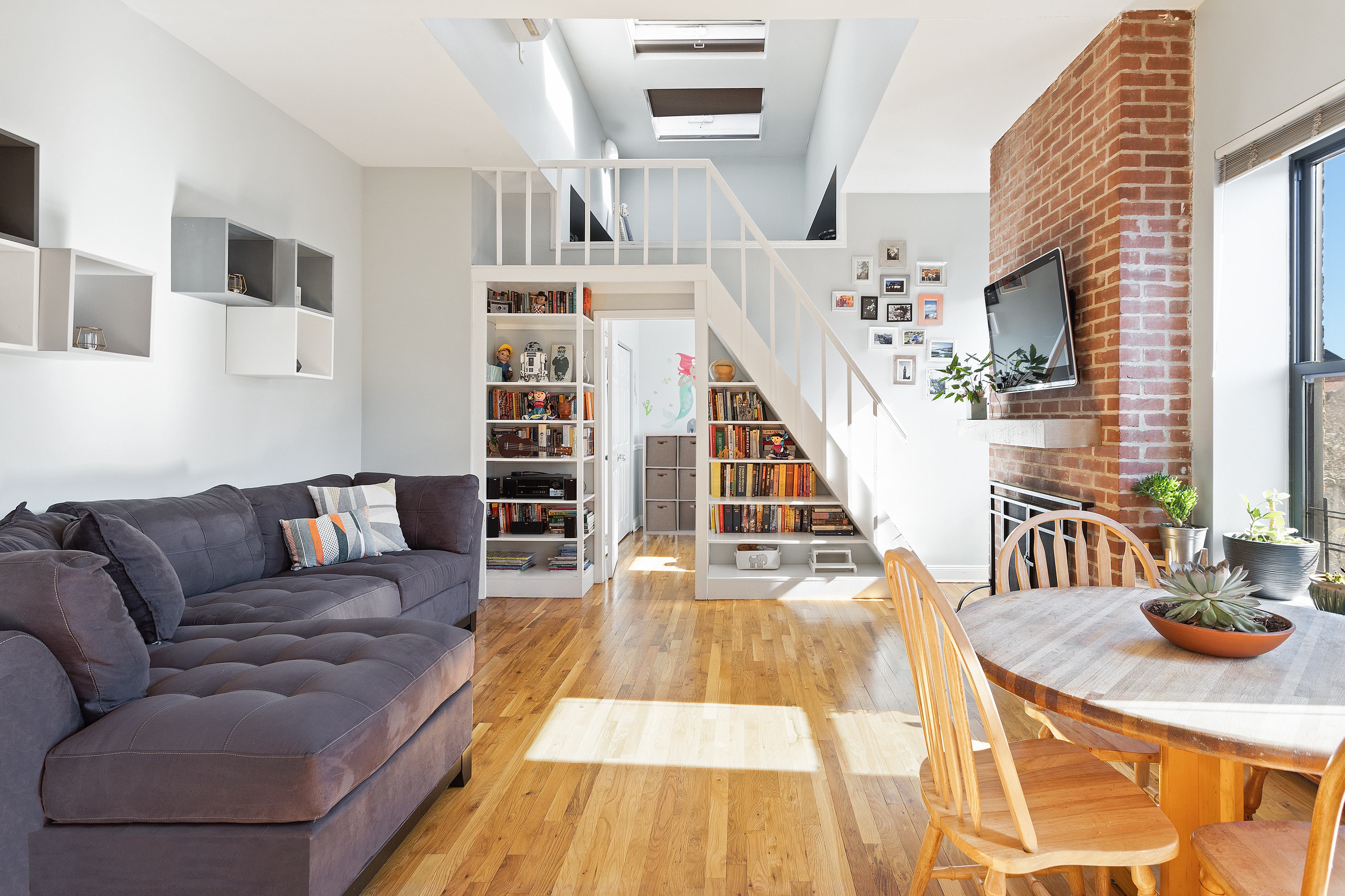 The living room has south-facing windows, a working fireplace surrounded by bricks, and a skylight.